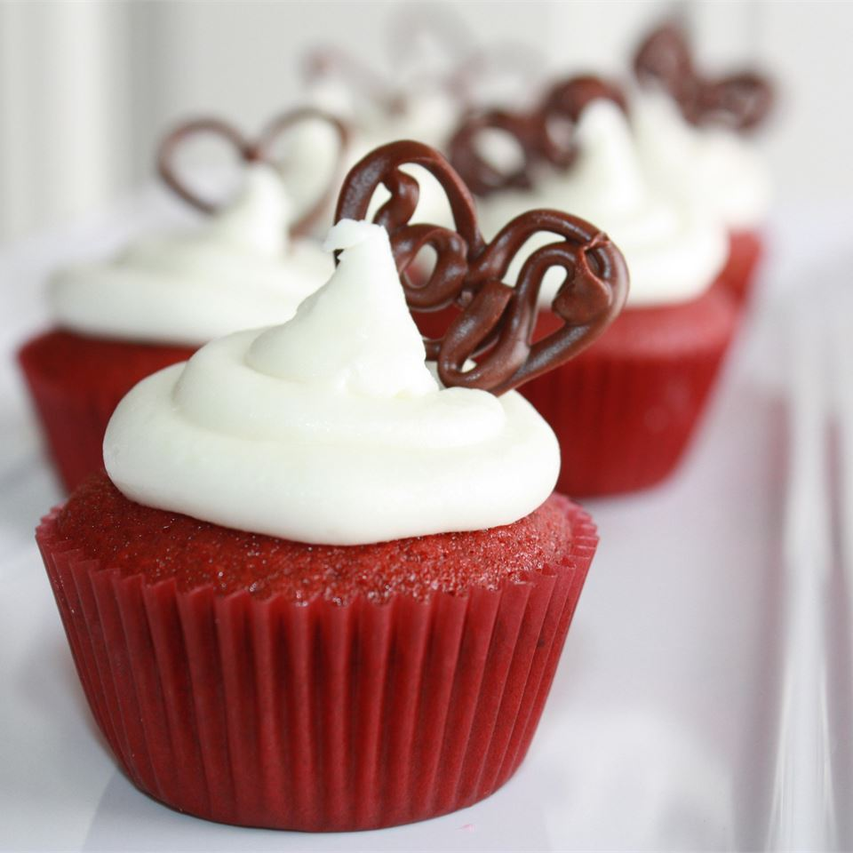 Moist Red Velvet Cupcakes with white frosting and chocolate garnish