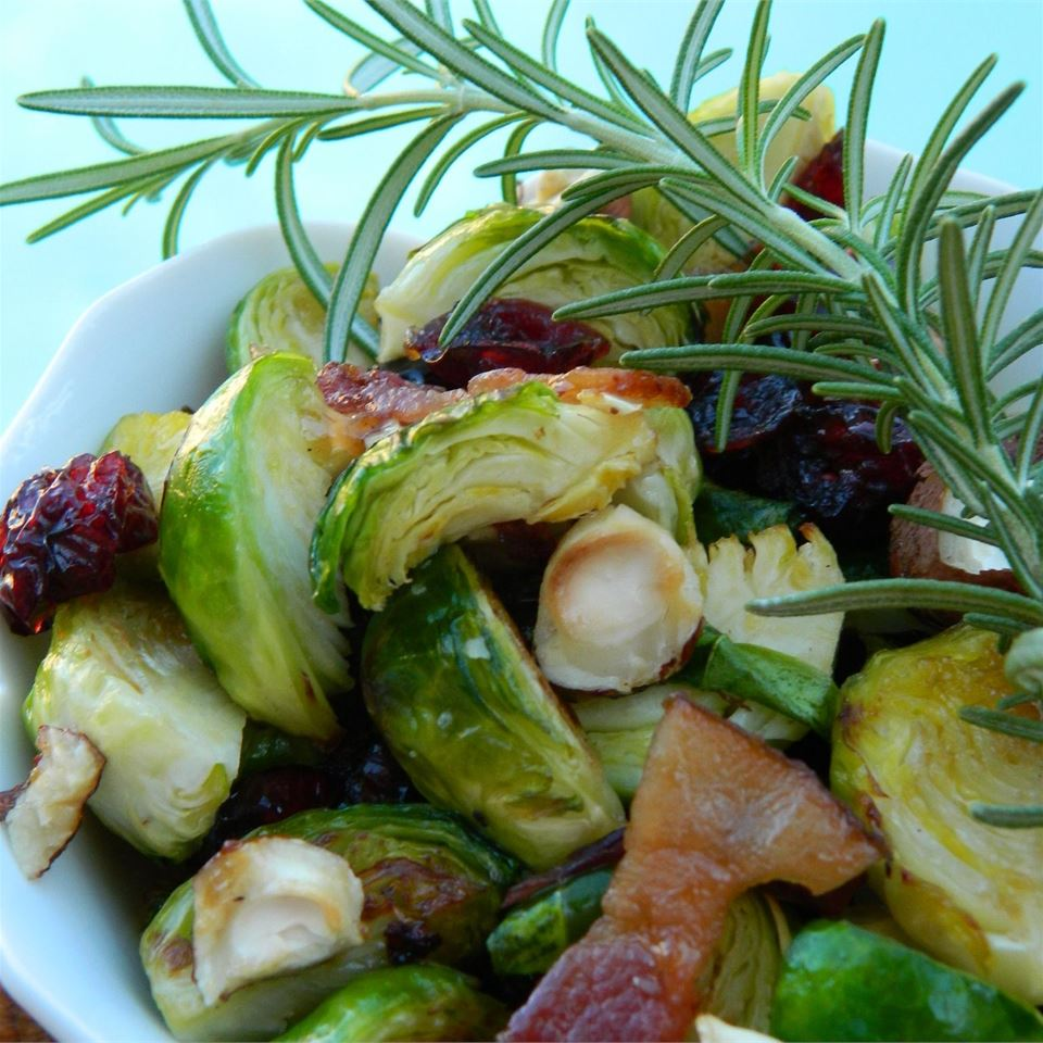 Warm Brussels Sprout Salad with Hazelnuts and Cranberries with rosemary garnish