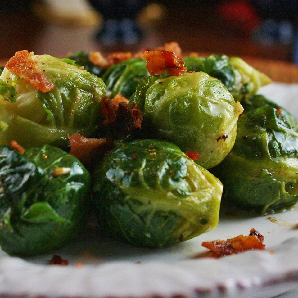 Garlic Brussels Sprouts with Crispy Bacon on a white plate