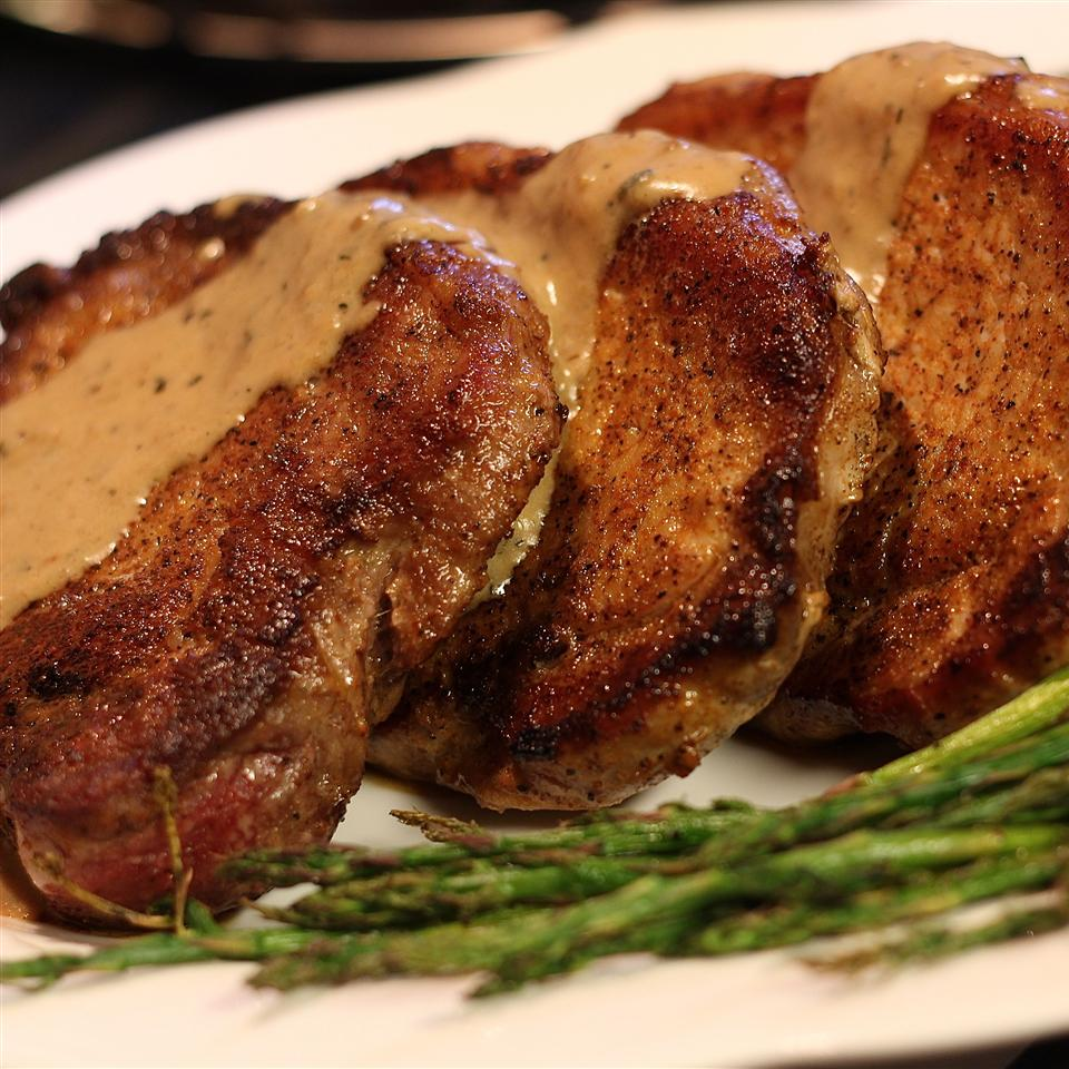 Pan-fried pork chops on a platter with gravy and asparagus
