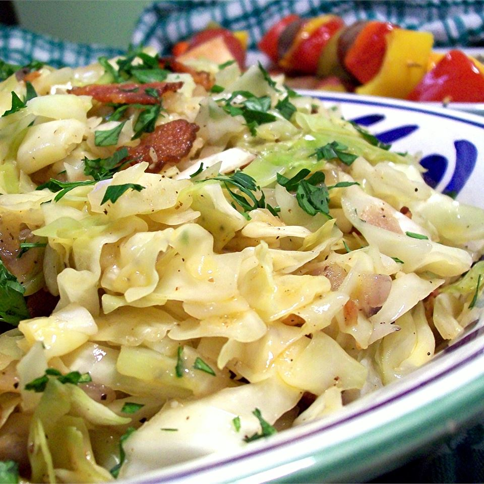 Fried Cabbage with Bacon, Onion, and Garlic on a white, green, and blue plate
