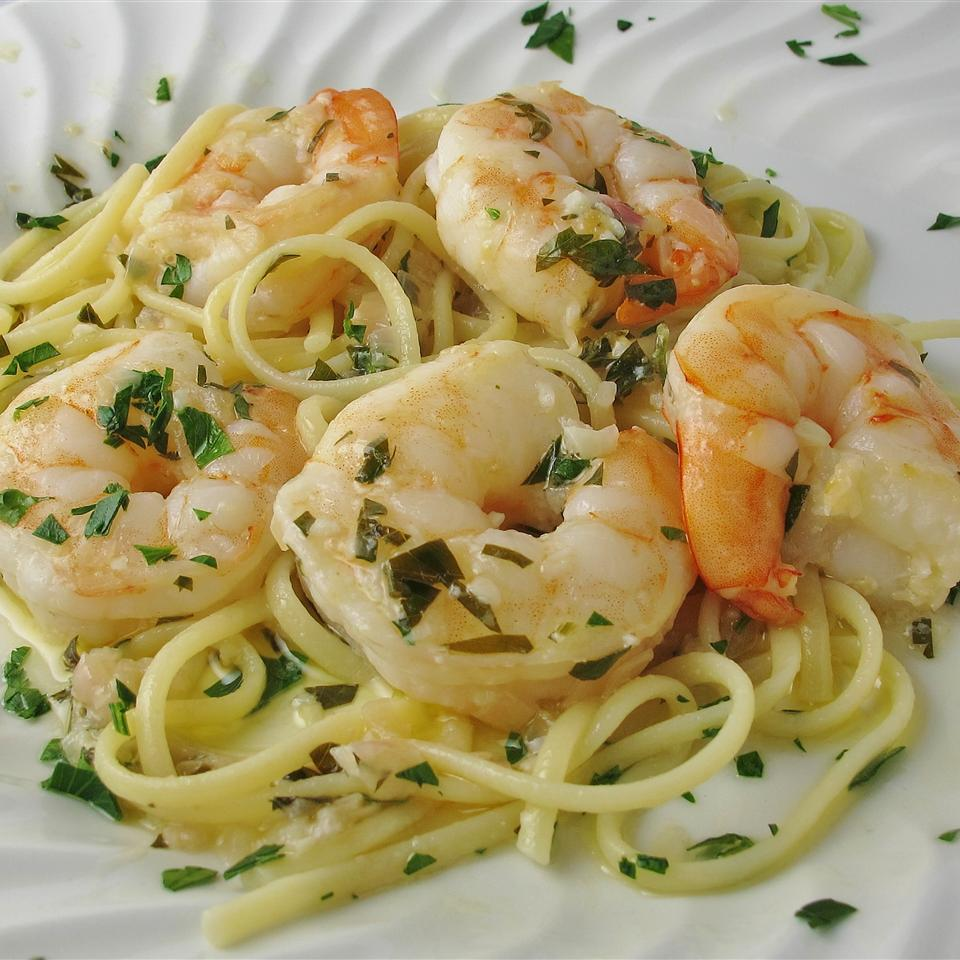 pasta with shrimp garnished with parsley on a white plate
