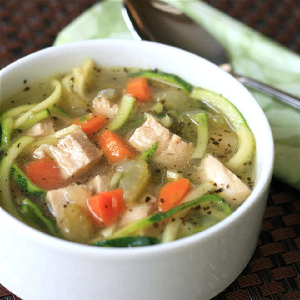 Chicken Zoodle Soup in white bowl with spoon in background