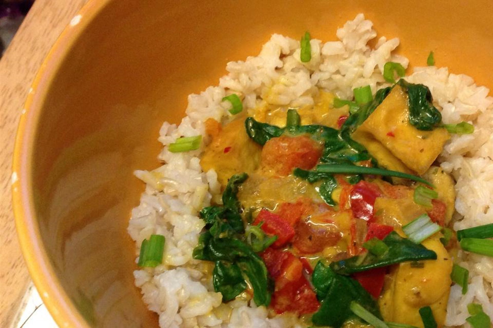 Coconut Curry Tofu over white rice in wooden bowl