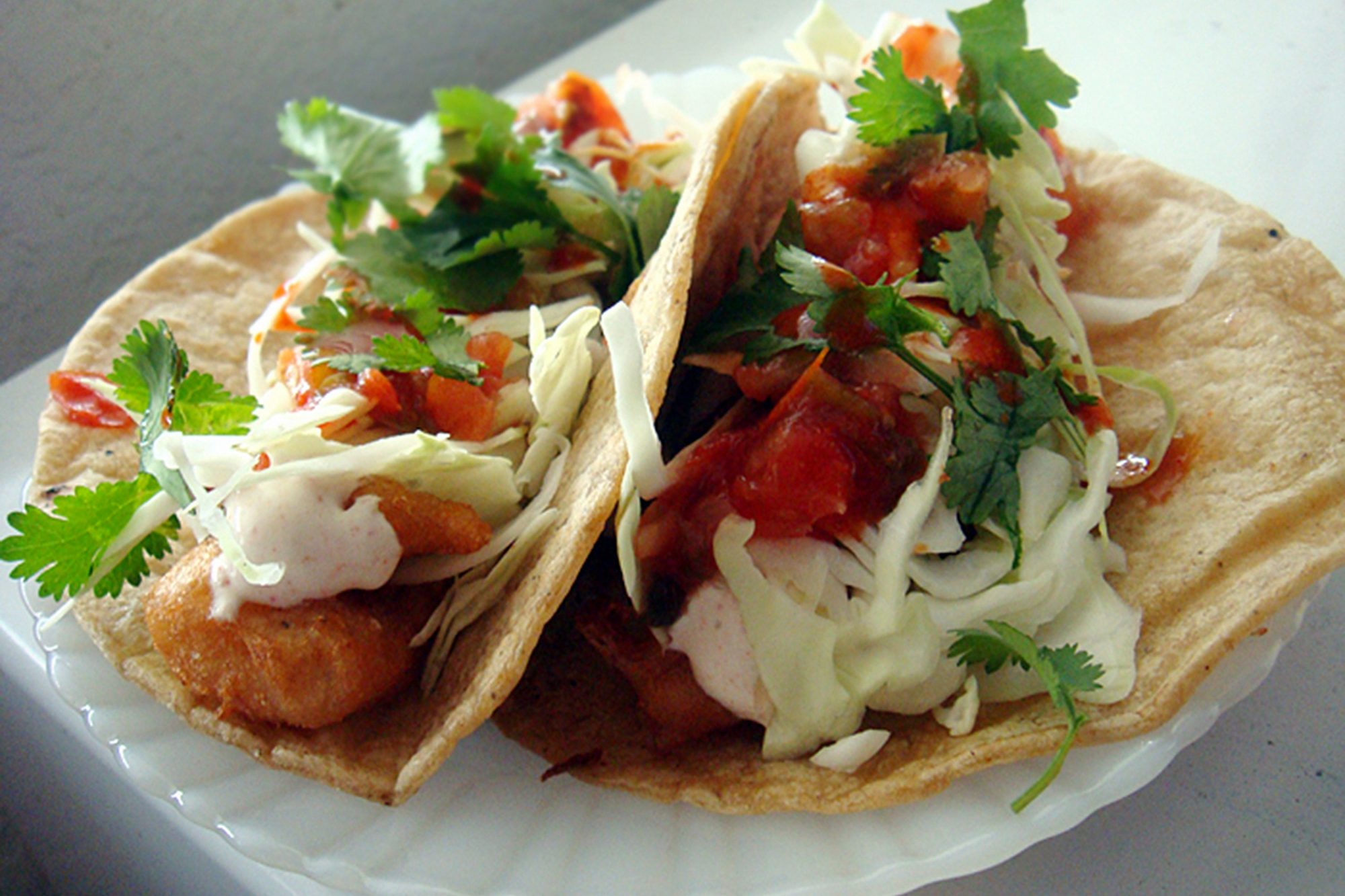 two fish tacos with toppings