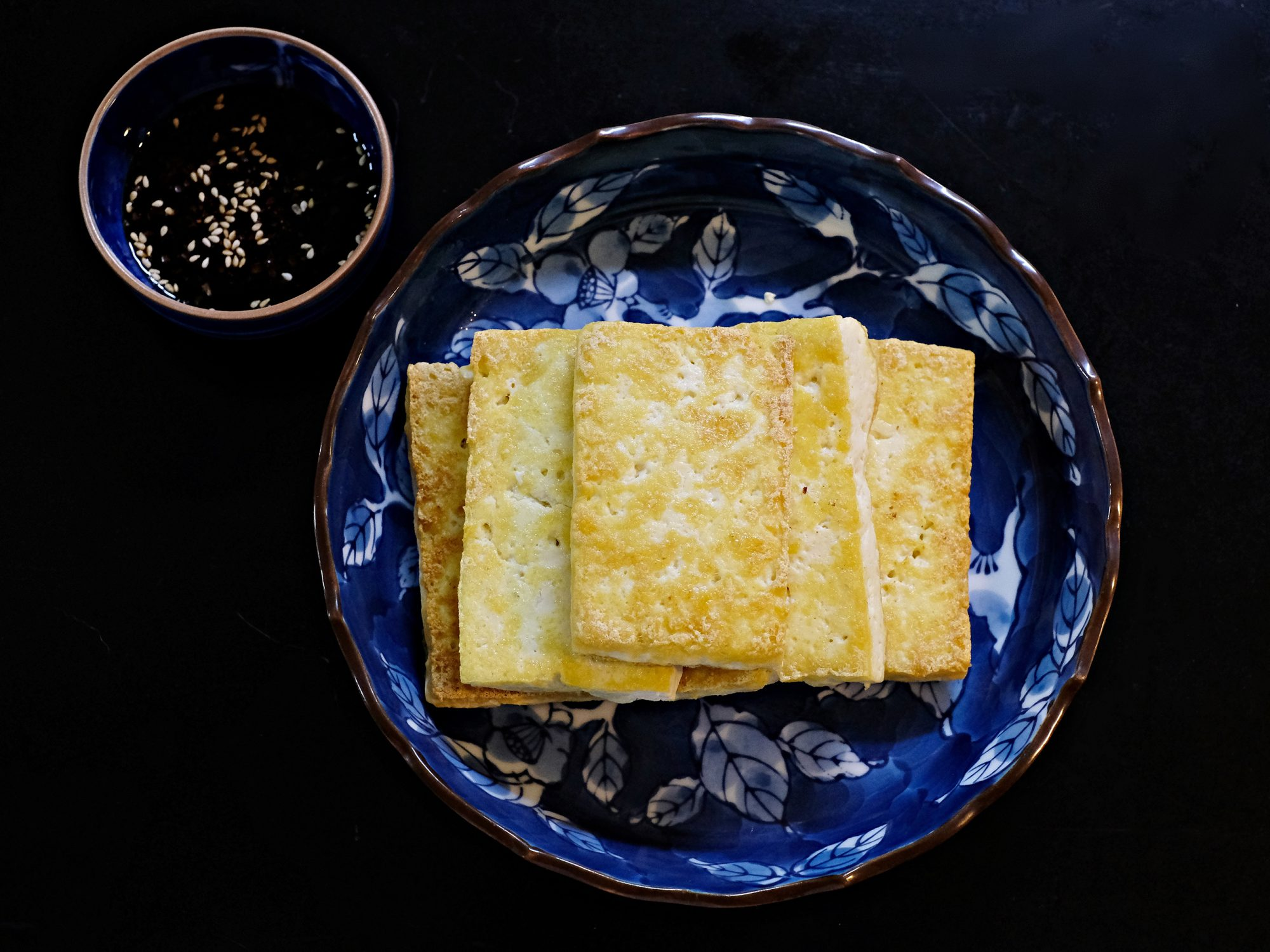 Pan fried crispy tofu is served with dipping soy sauce.