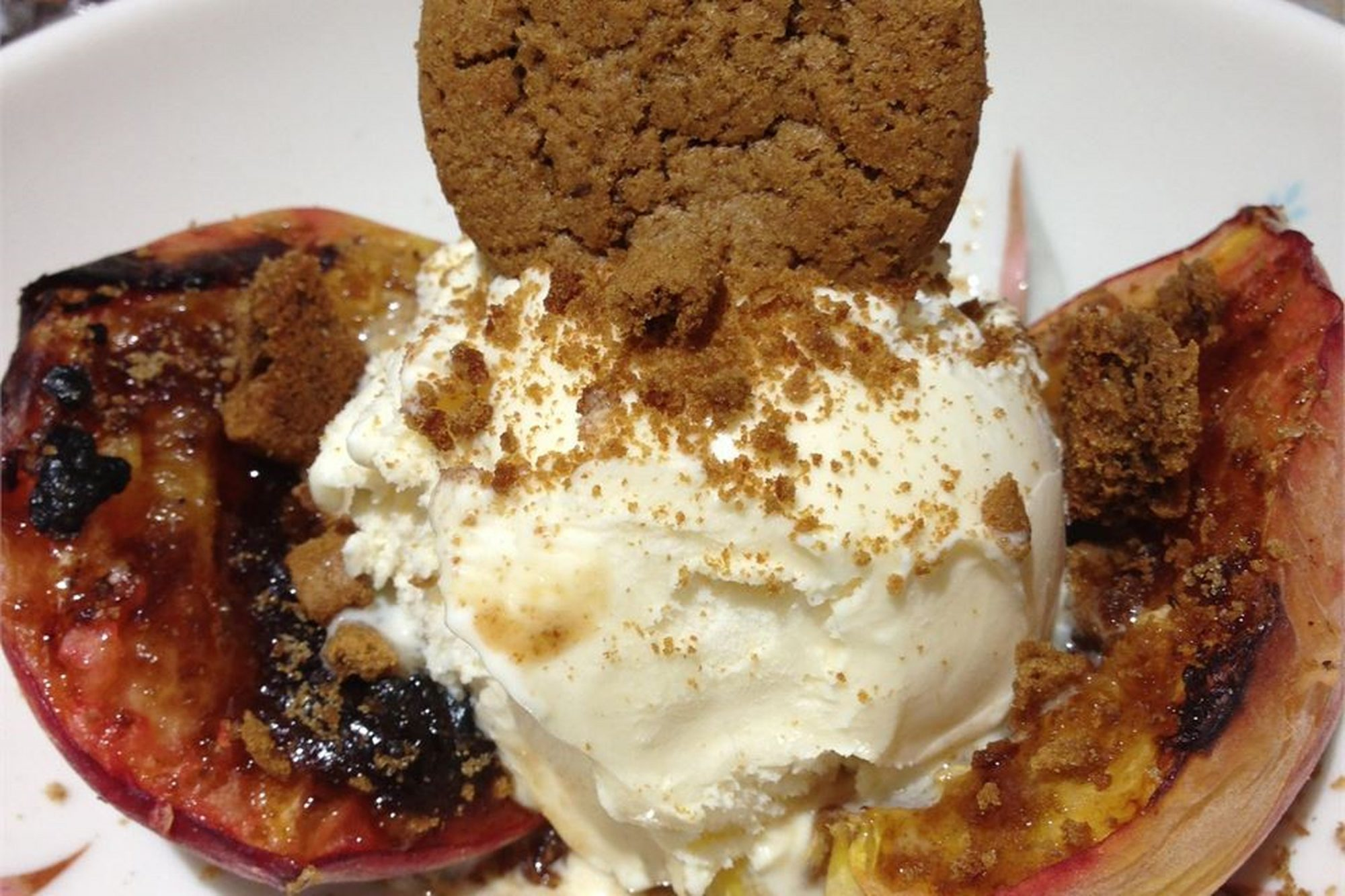 Grilled Peaches with Gingersnaps and ice cream in a bowl