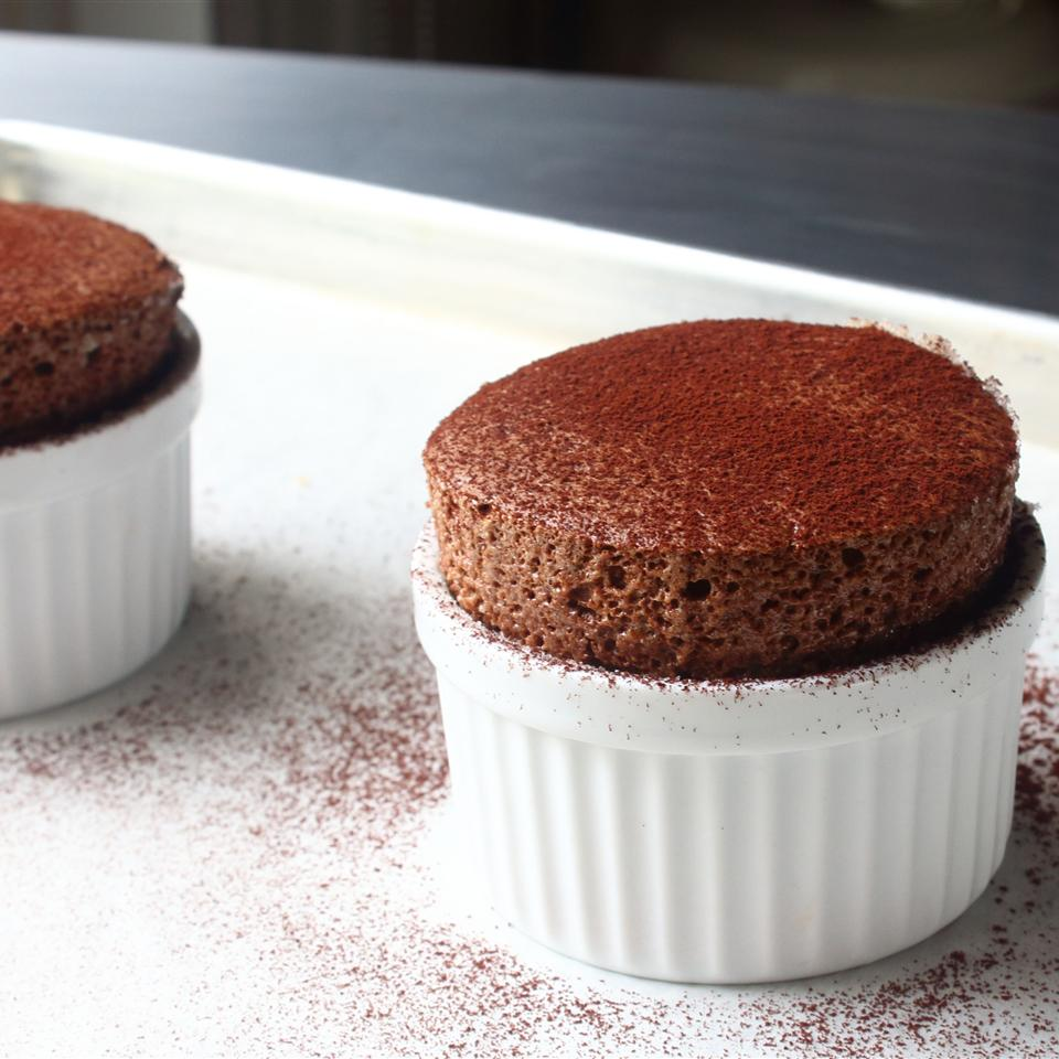 dark chocolate souffle standing tall in a white souffle cup