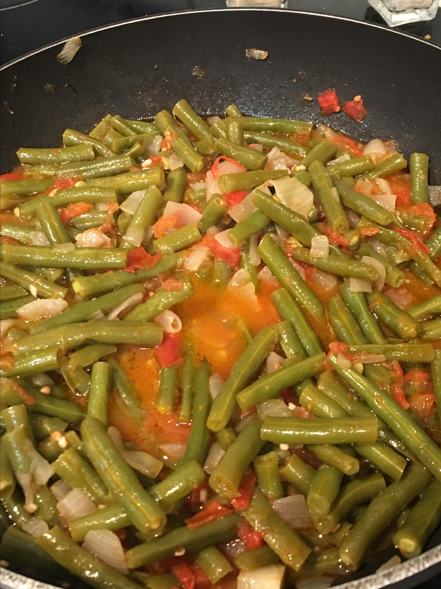 a pan of green beans with onions and tomatoes simmering in a red liquid