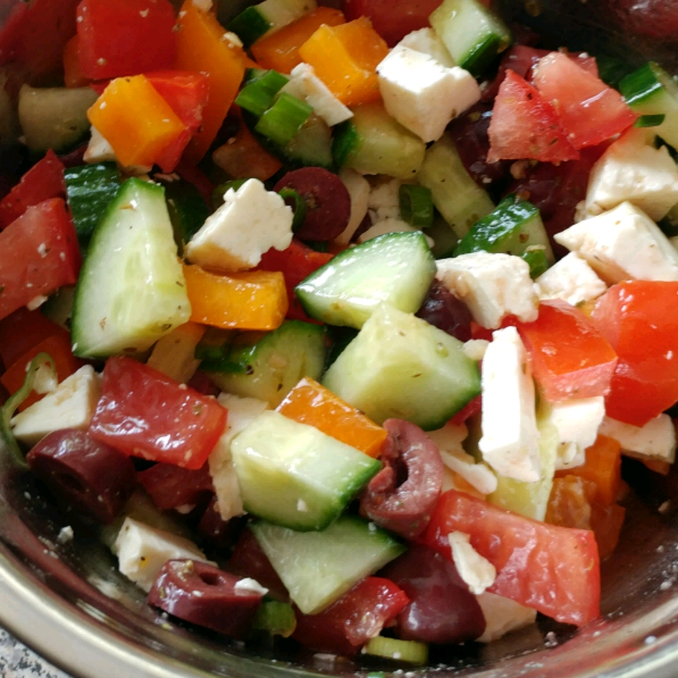 Greek salad with cucumber, pepper, tomato, olive, and feta pieces