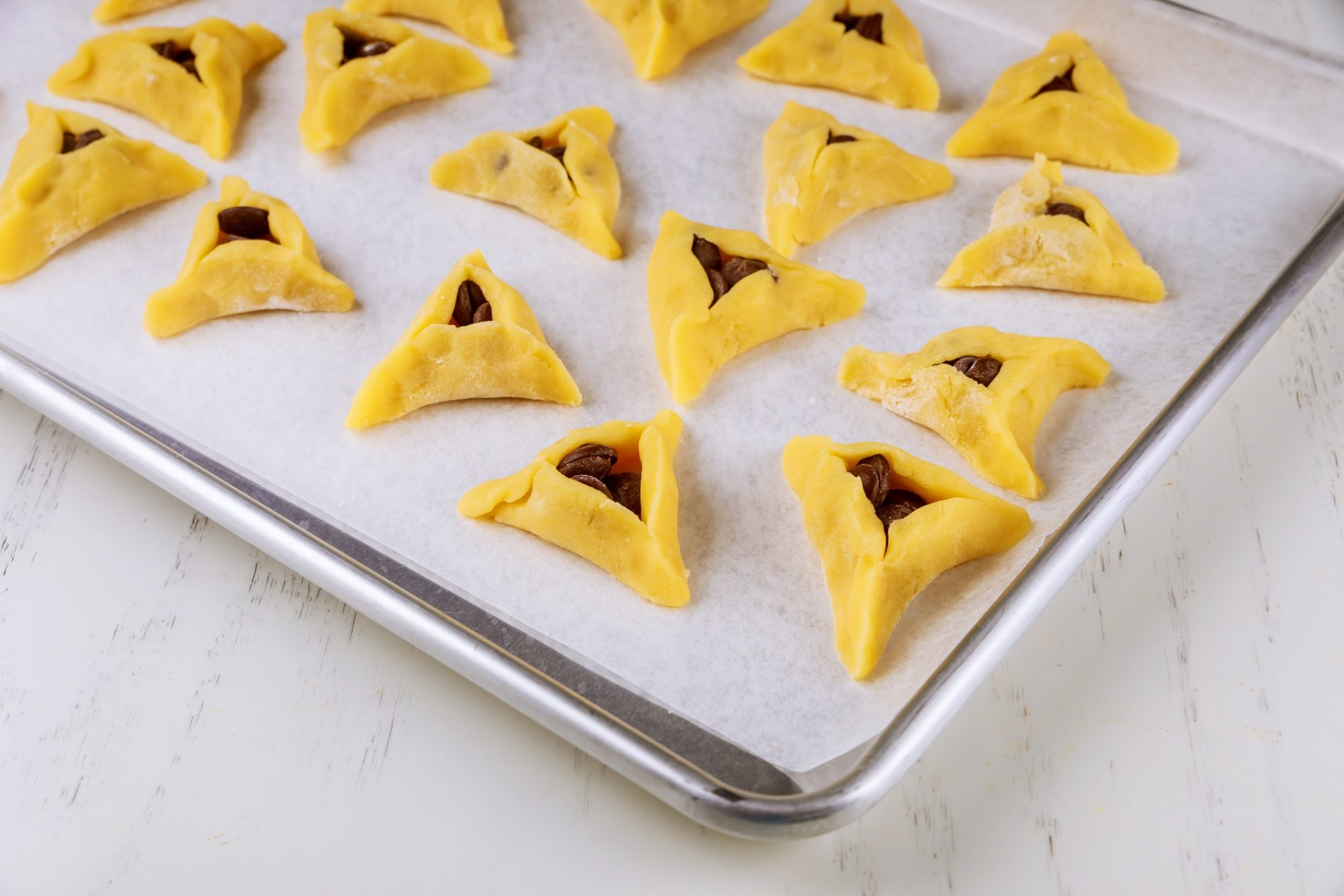 hamantaschen on a cooking sheet ready to bake