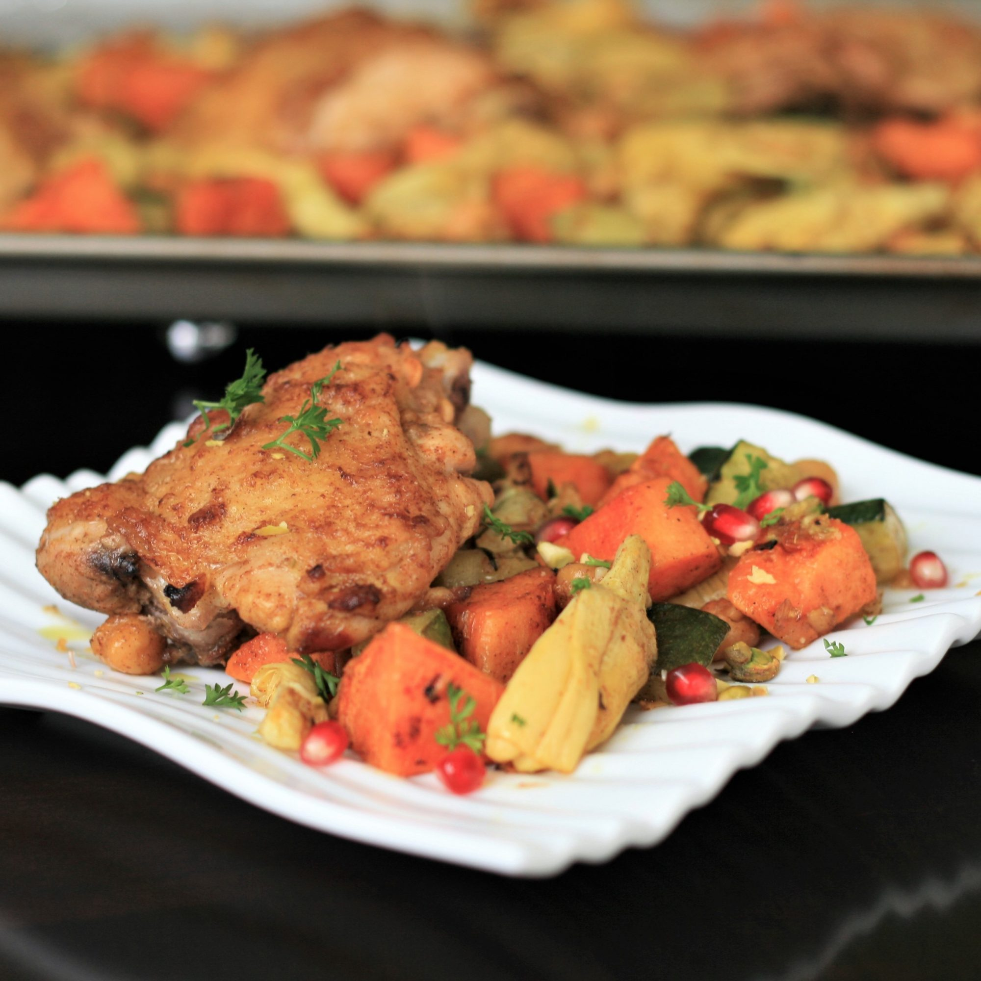 a square white plate with chicken and roasted vegetables in the foreground, with a sheet pan of chicken in the background
