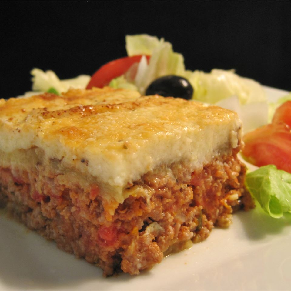 a slice of layered moussaka shows mashed potatoes on top with beef-vegetable mixture on bottom