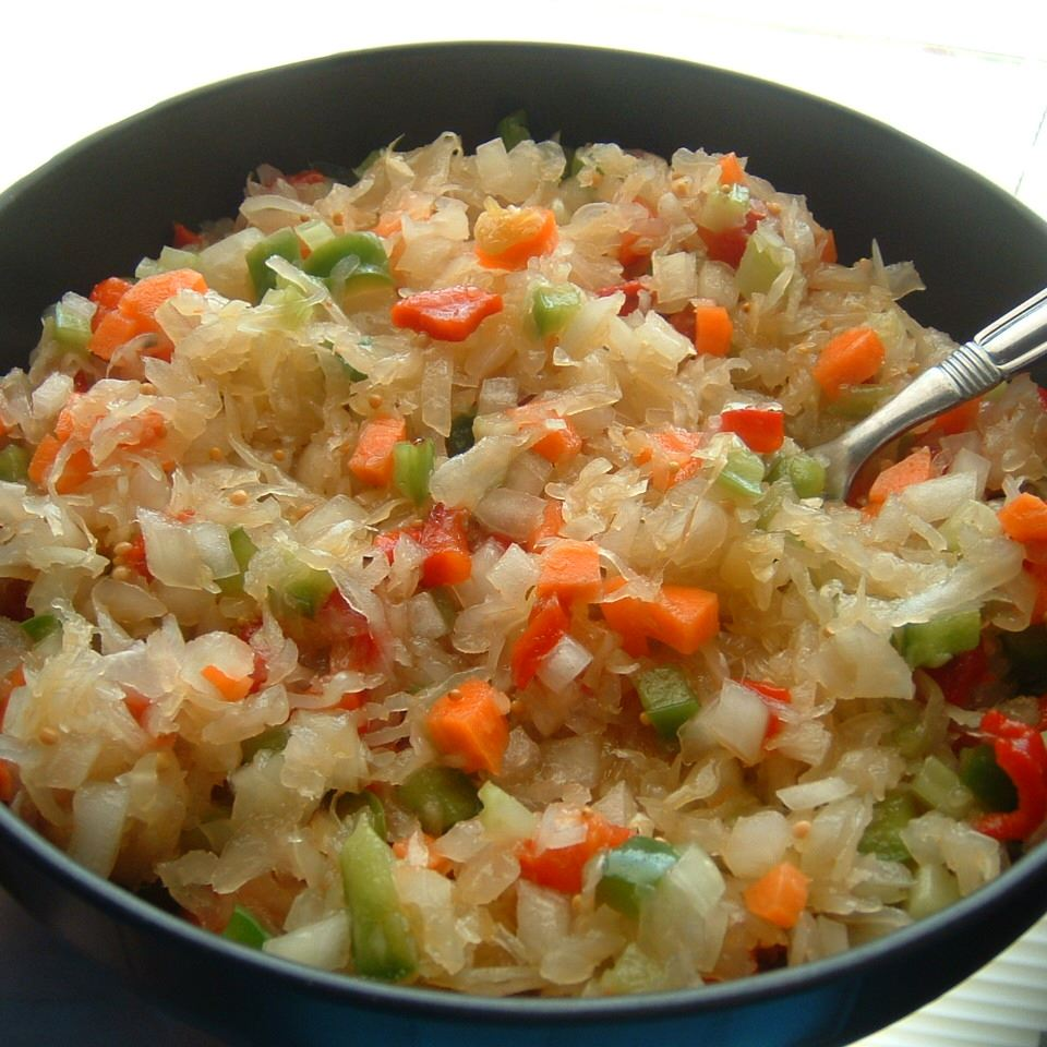 a bowl of yellowed sauerkraut with pieces of carrot and green bell pepper