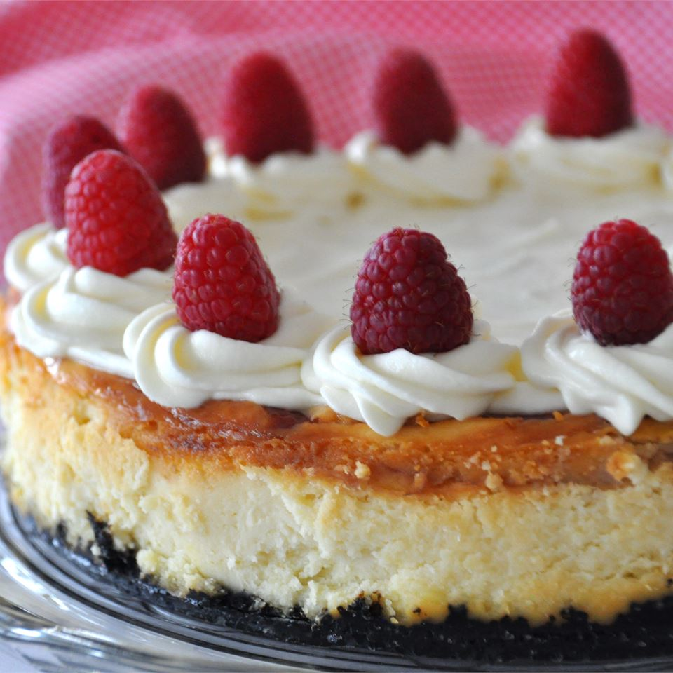 White Chocolate Raspberry Cheesecake decorated with raspberries on top