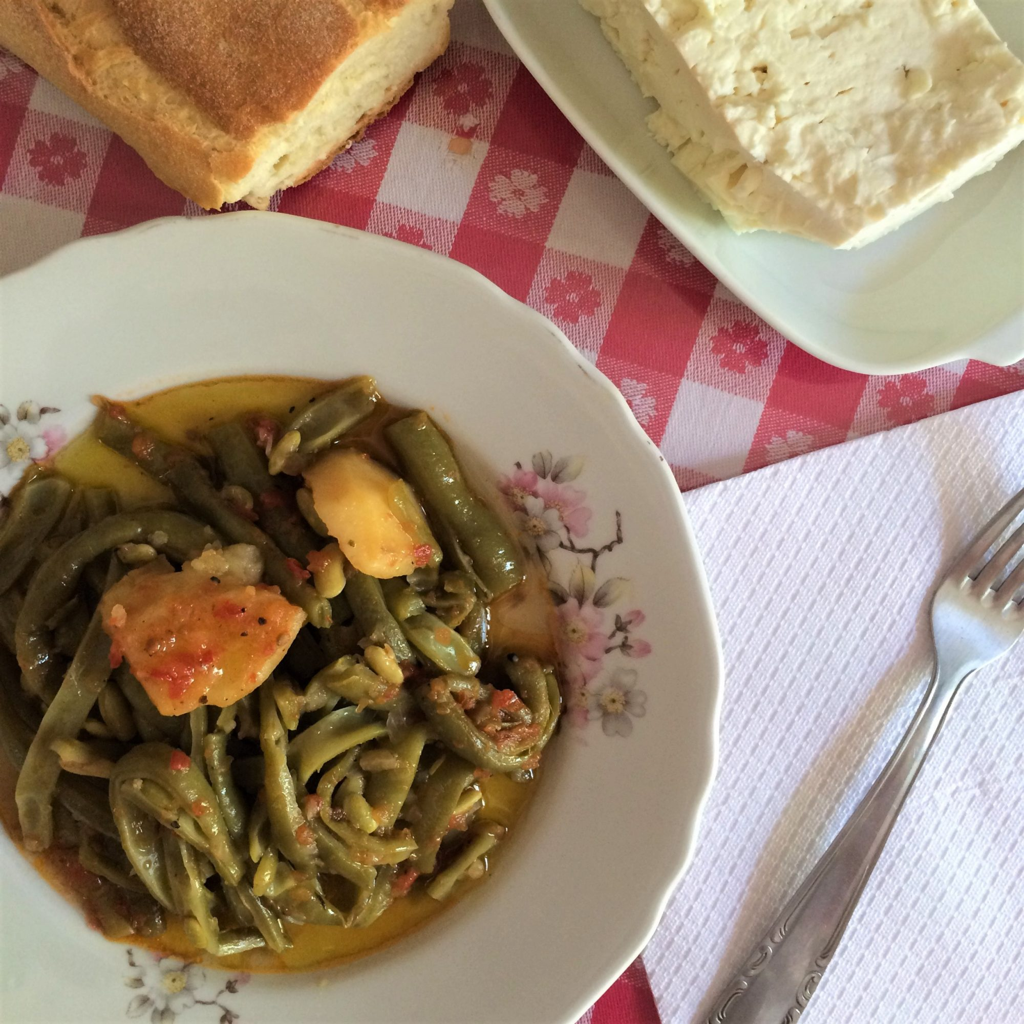 A typical Greek meal of fasolakia green beans with bread and feta cheese on the side.