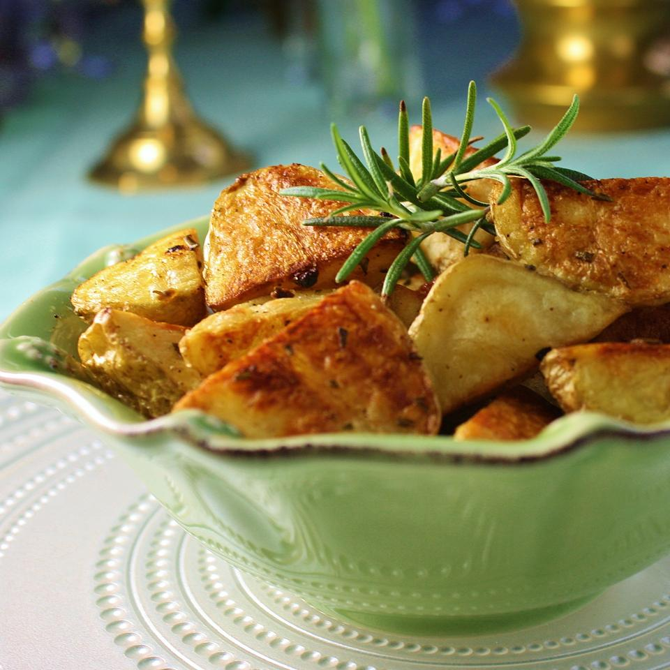 roasted potatoes in a green bowl with rosemary garnish
