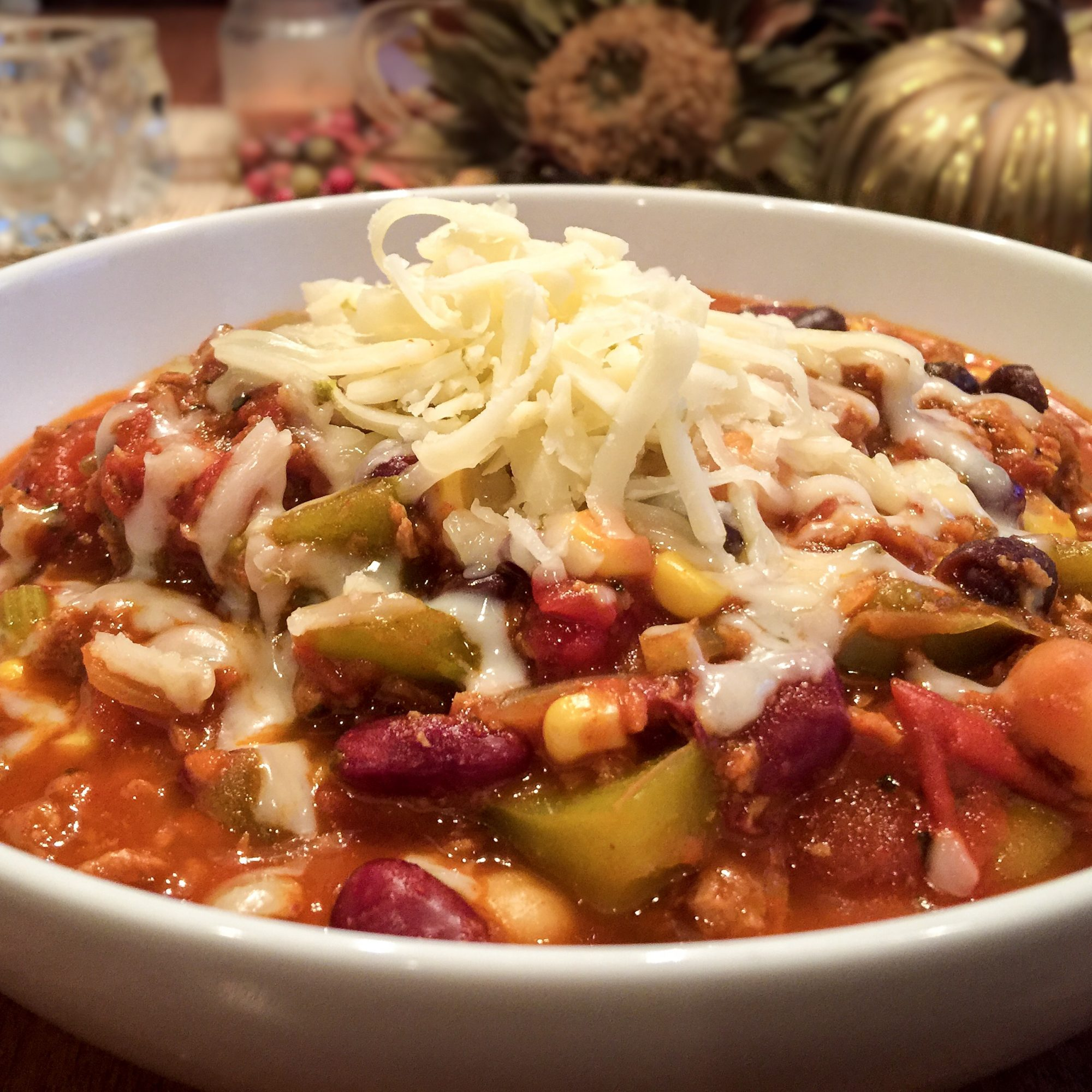 The Best Vegetarian Chili in the World in a white bowl topped with cheese