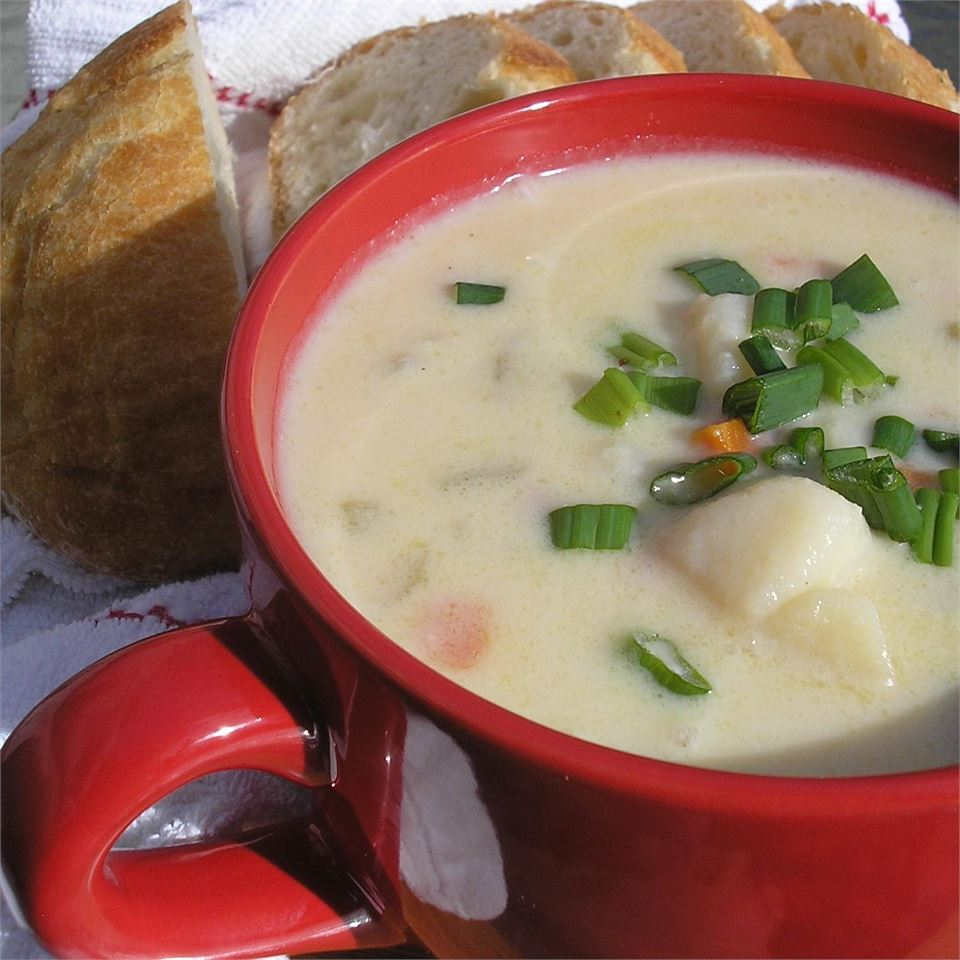 a red bowl of creamy soup with chunks of potato, garnished with sliced green onions with sliced bread in the background