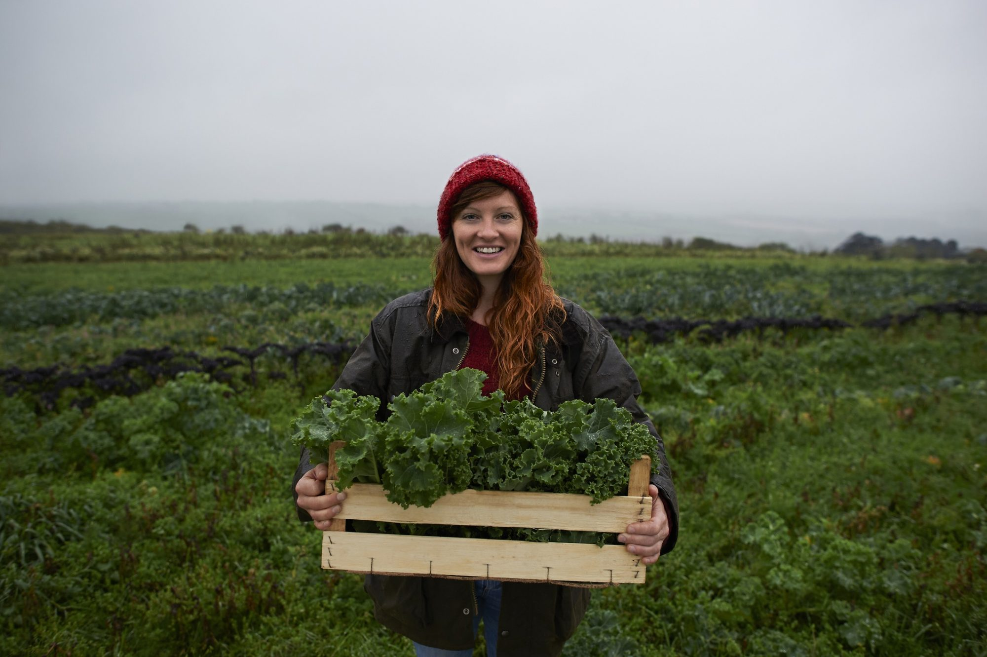 woman farmer with box of kale