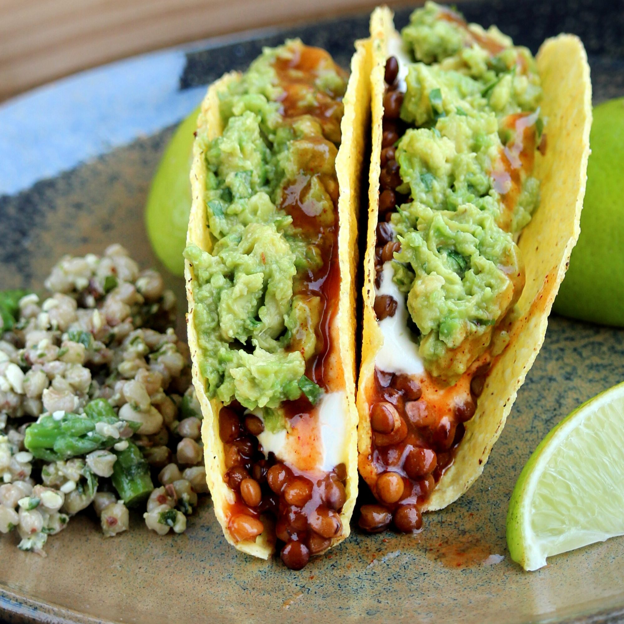 lentils in hard taco shell with sour cream and guacamole
