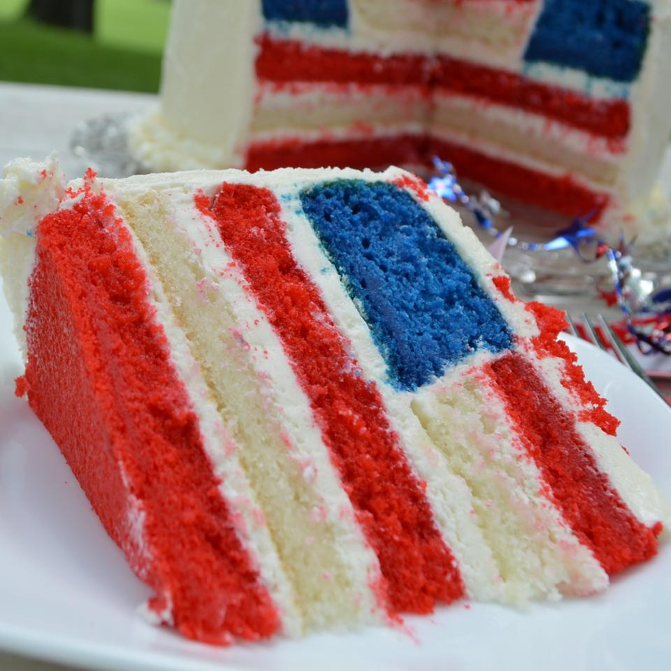 A slice of layer cake with red and white cake layers and a blue square