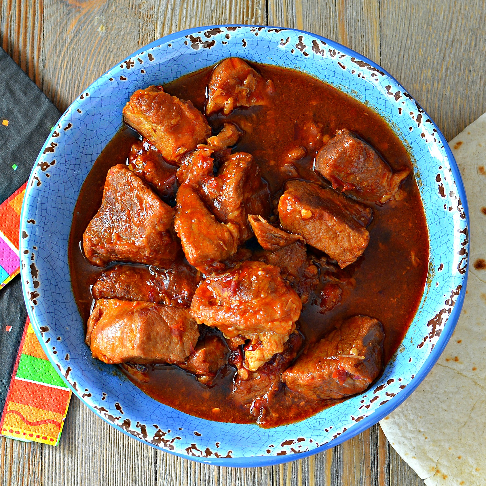 A blue bowl filled with chunks of beef in a red chile sauce
