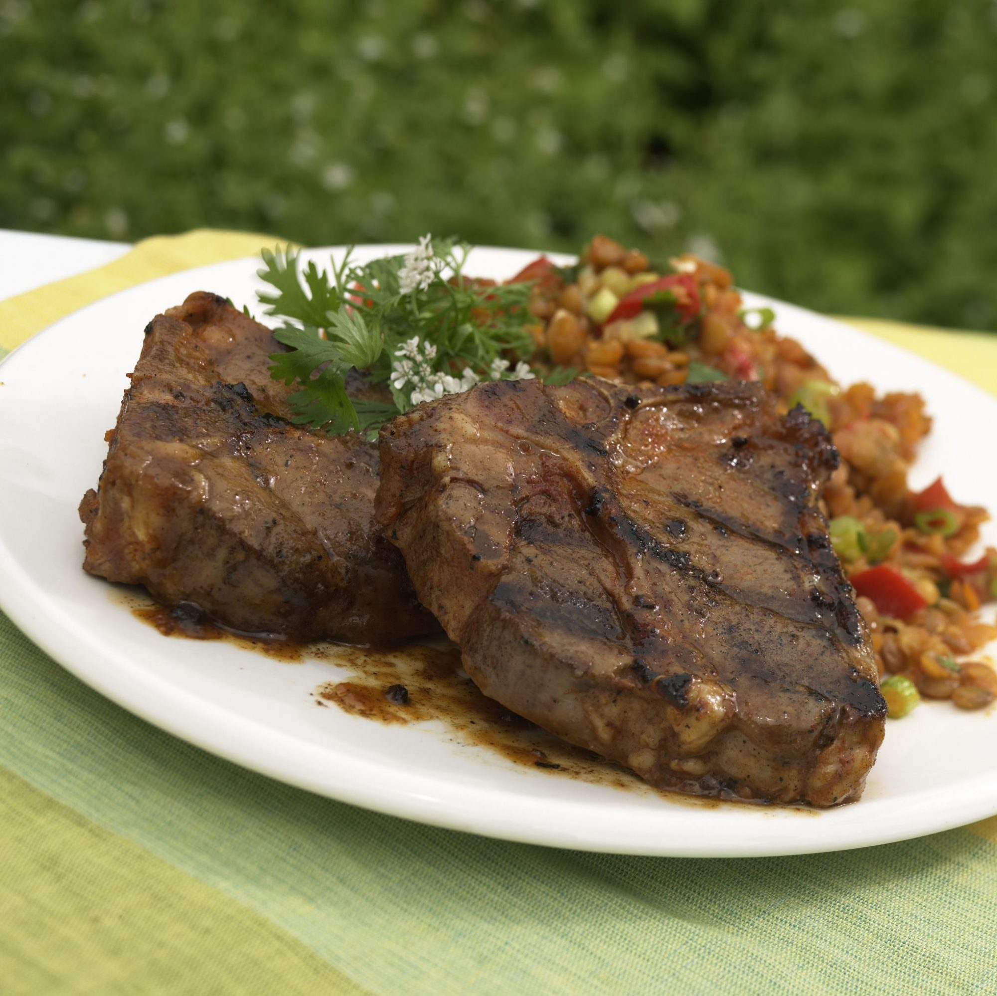 Grilled lamb shoulder chops on white plate with rice side