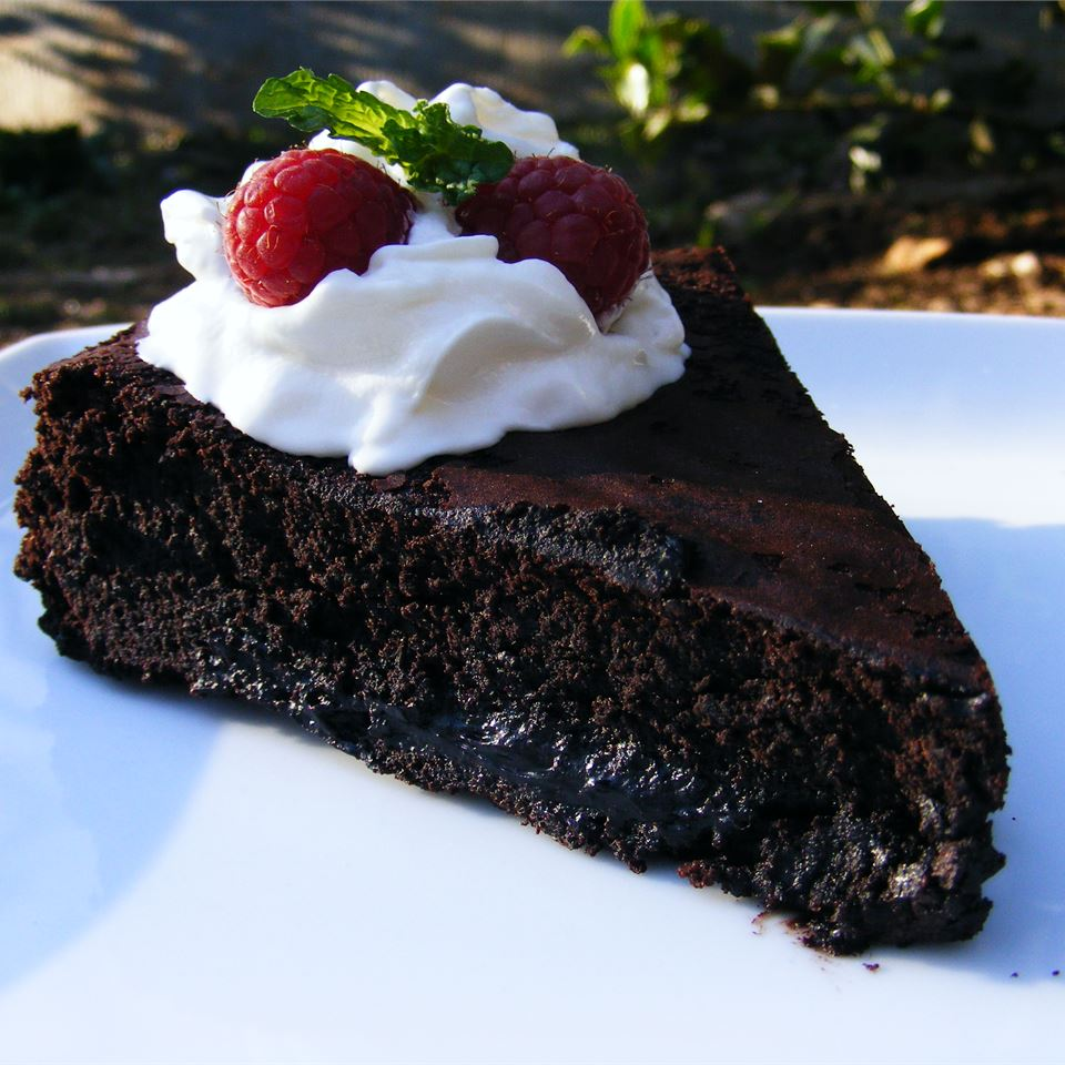 Slice of Flourless Chocolate Cake with Caramel Sauce, whipped cream and berries