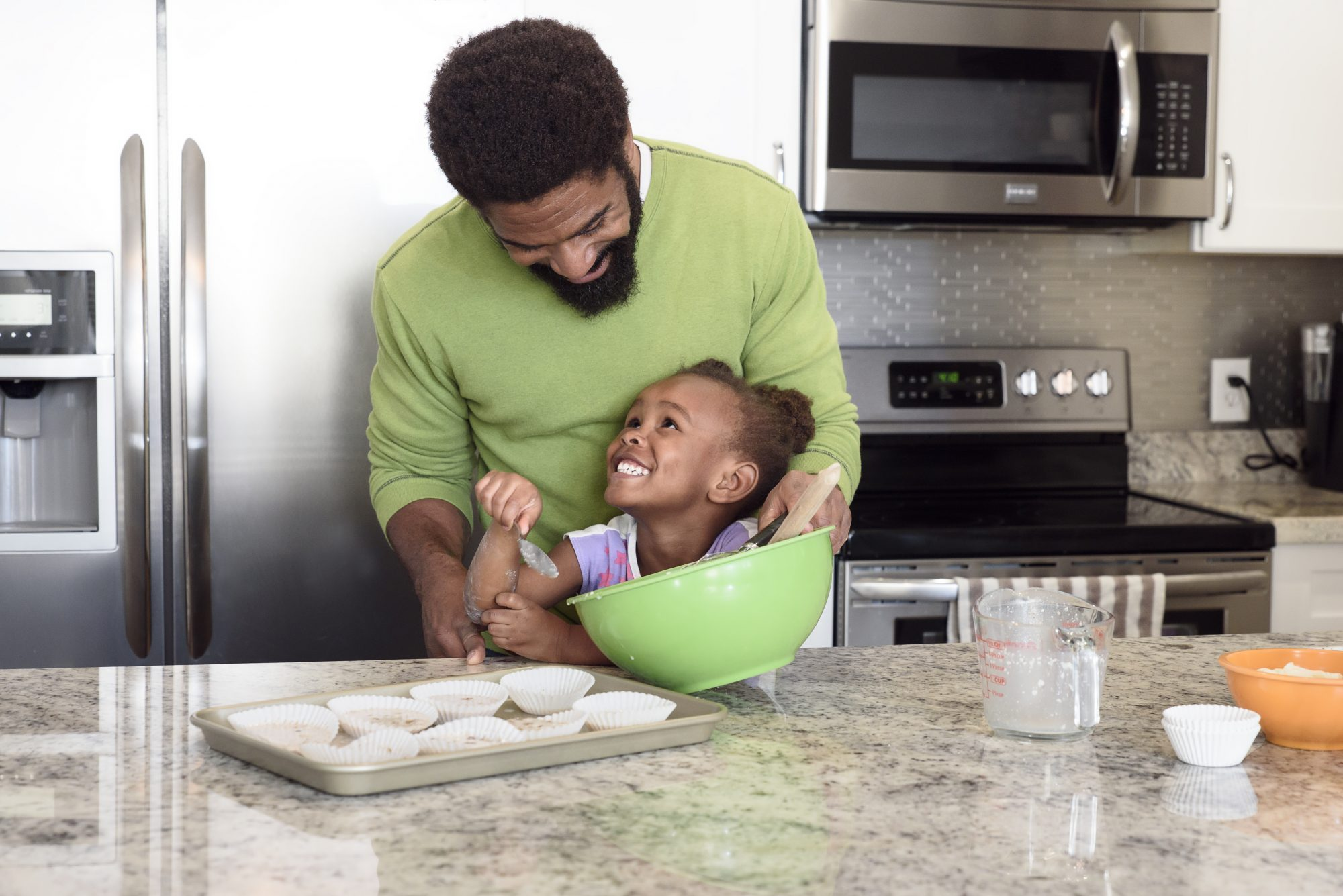 Little girl home baking with her father