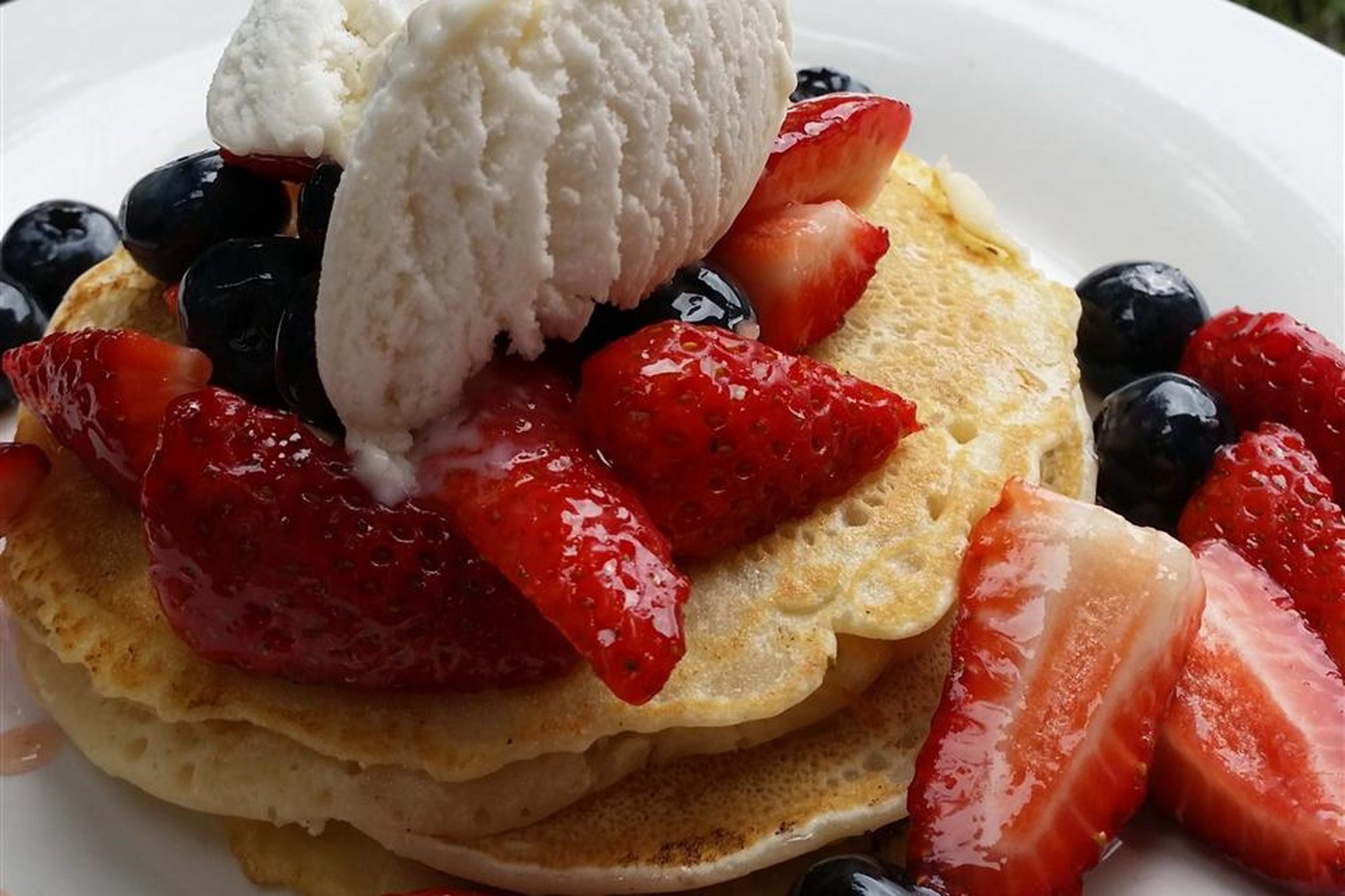 Vegan pancakes with strawberries, blueberries, and ice cream