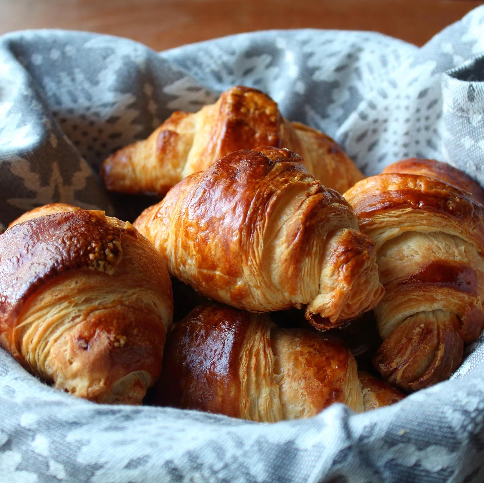 Croissants in a blue cloth-lined basket