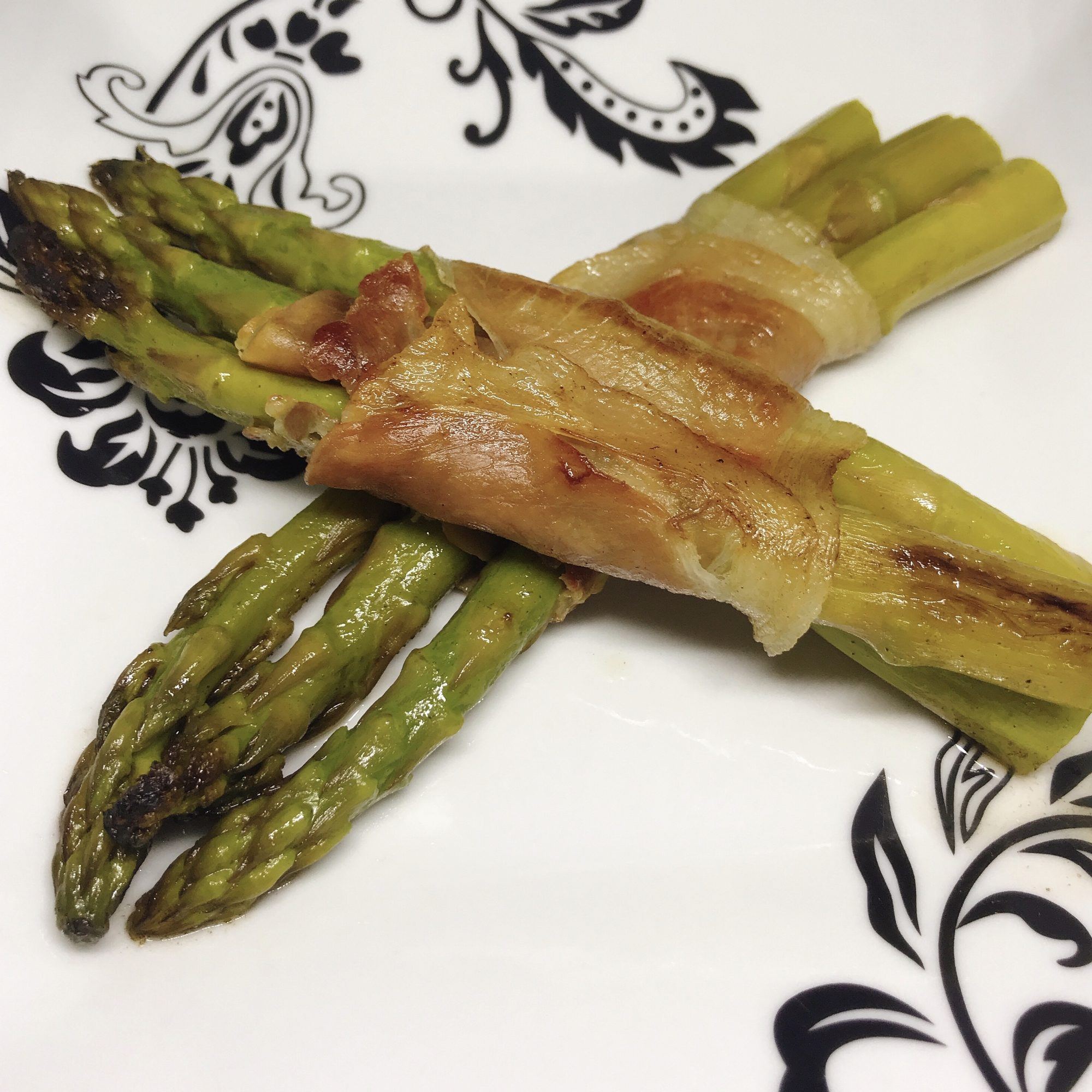 prosciutto-wrapped asparagus on white plate
