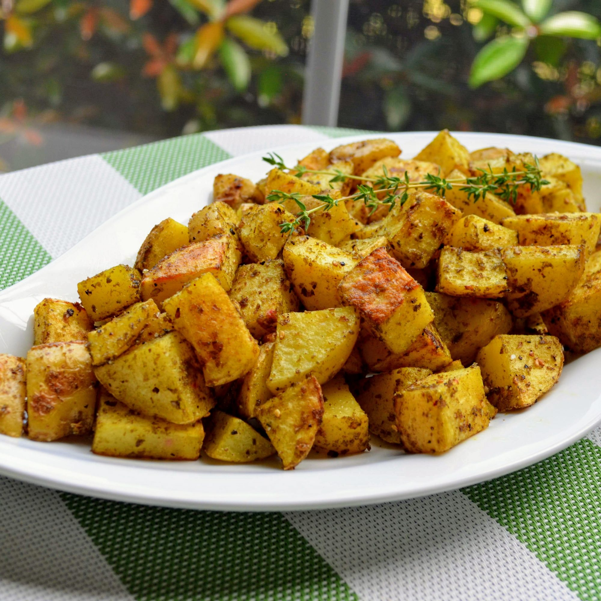 Za'atar Roasted Potatoes in a white dish on a green and white tablecloth