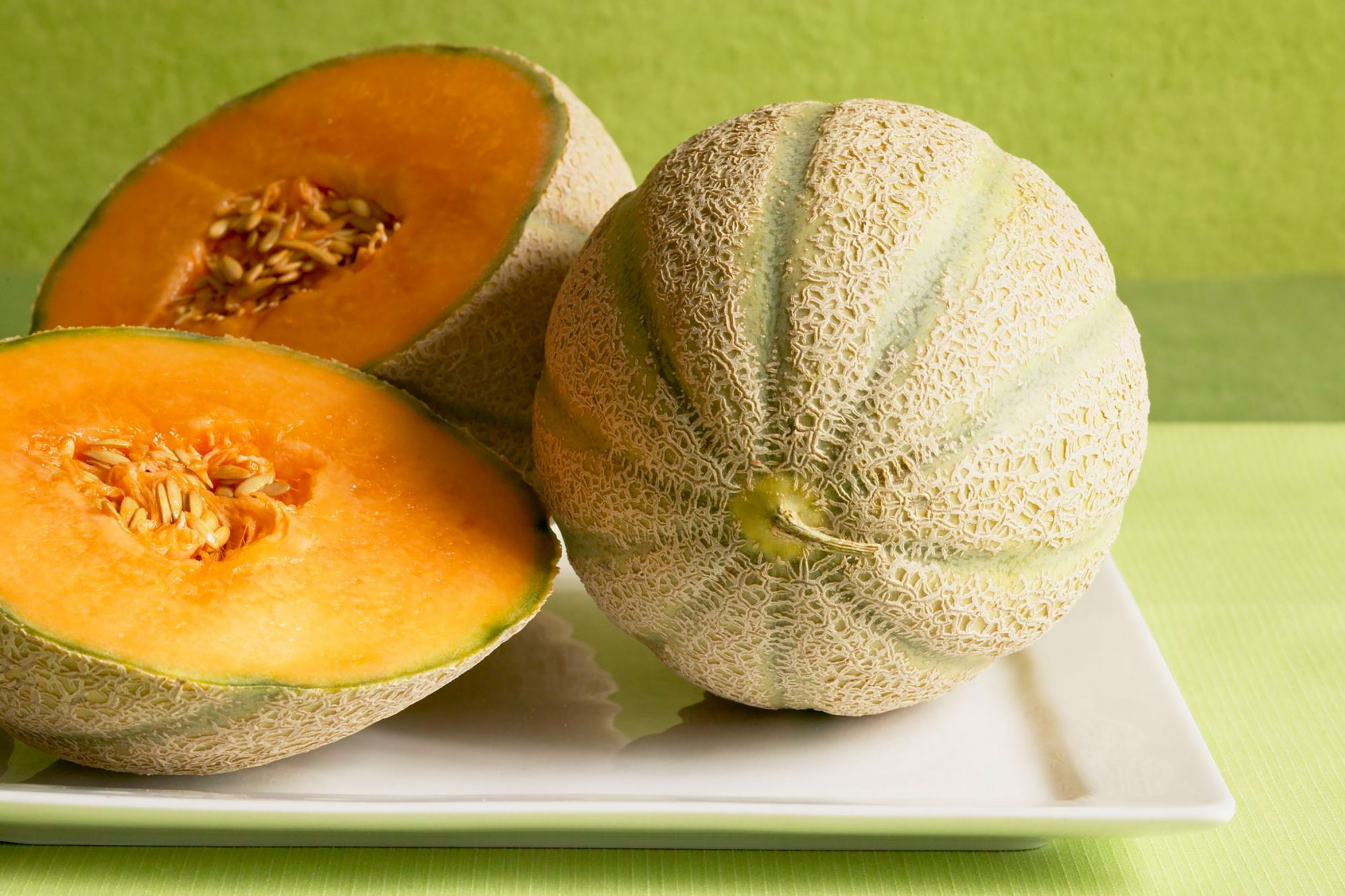Cantaloupe sliced on white plate with green background