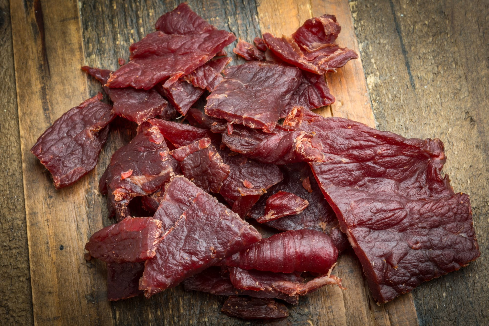 Heap of Beef Jerky over a wooden counter close up