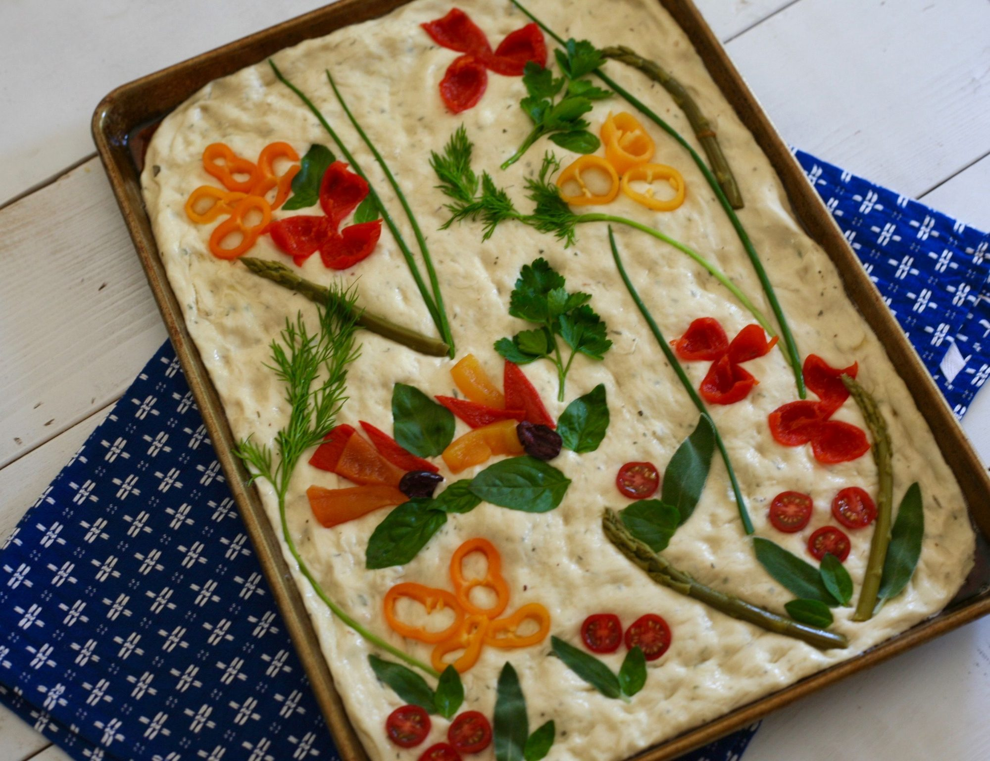 decorating focaccia dough with vegetables and herbs