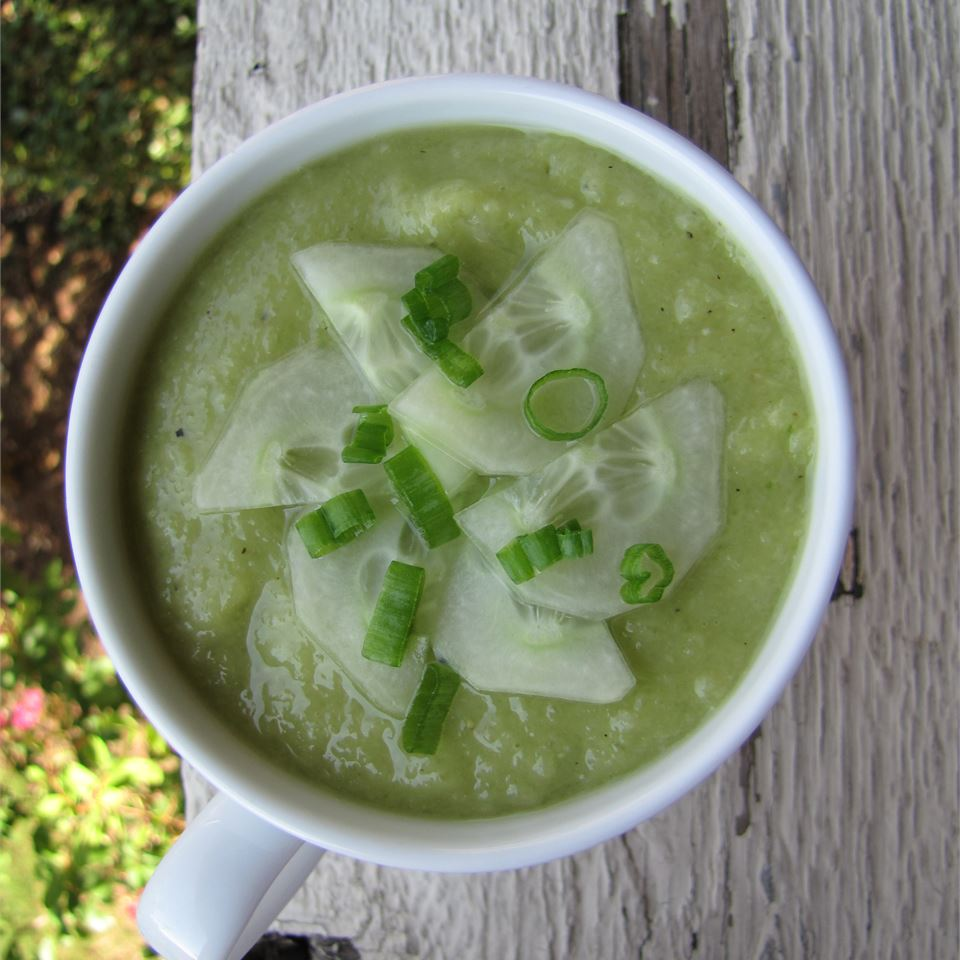top-down view of a white china cup filled with chilled soup garnished with cucumber slices and chives