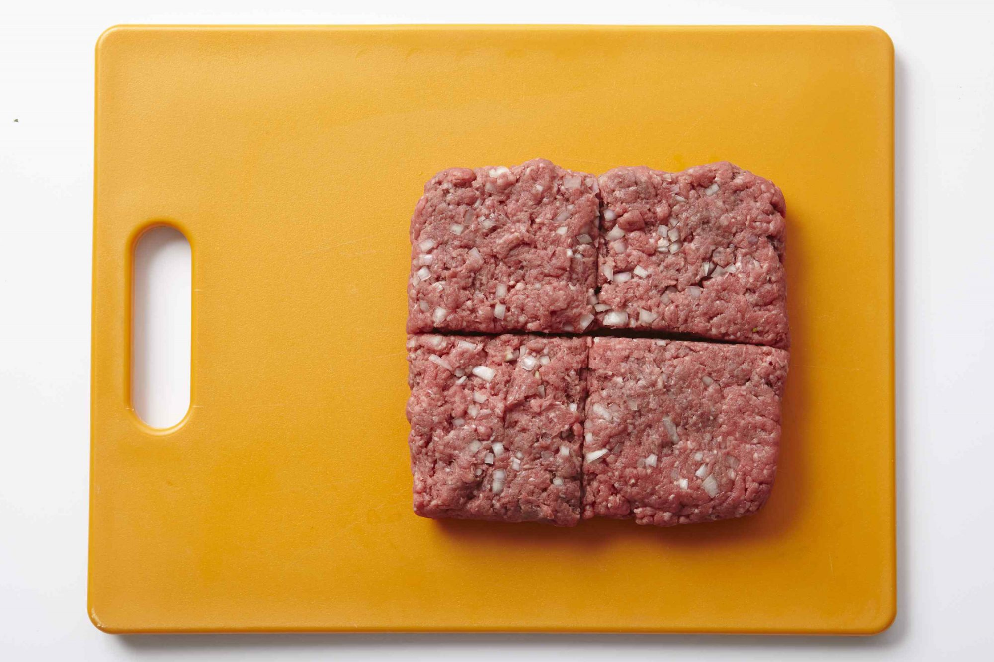 ground beef squared on yellow cutting board