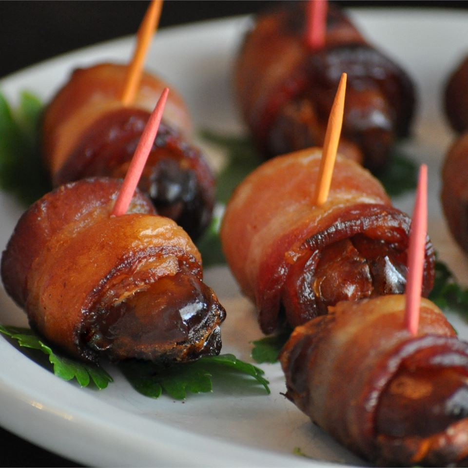 "Sweet dates are stuffed with almonds, wrapped in bacon, and broiled until the bacon is crispy. ""This is SO delicious,"" says FIVEINKENYA. ""It's sweet, chewy, crispy and so unique. And just as good without the almonds."""