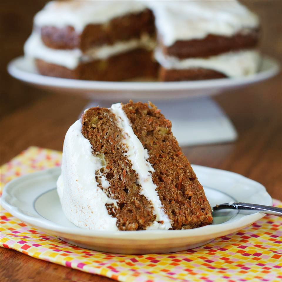 slice of carrot cake on a white plate with the cake in the background