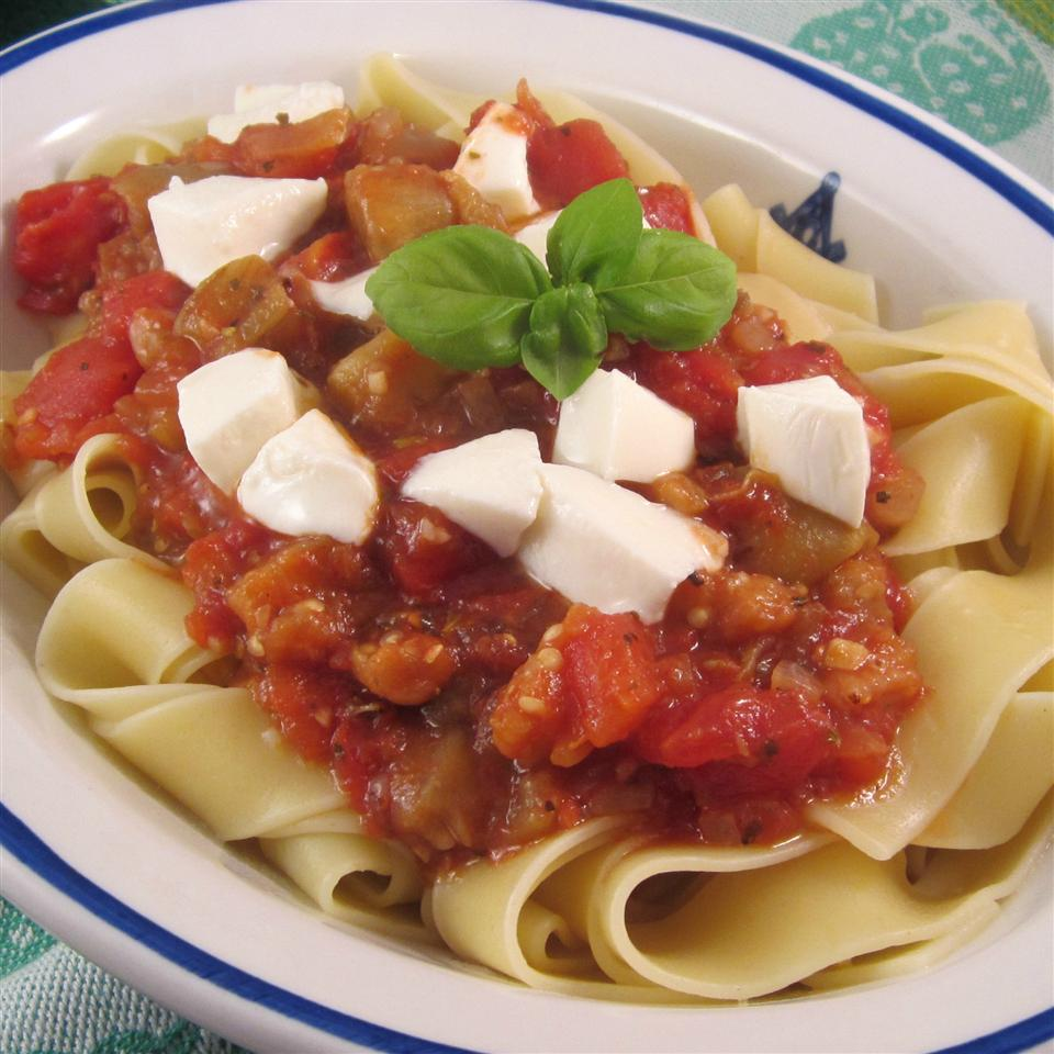 Mediterranean-Style Eggplant Pasta topped with cheese in a white bowl