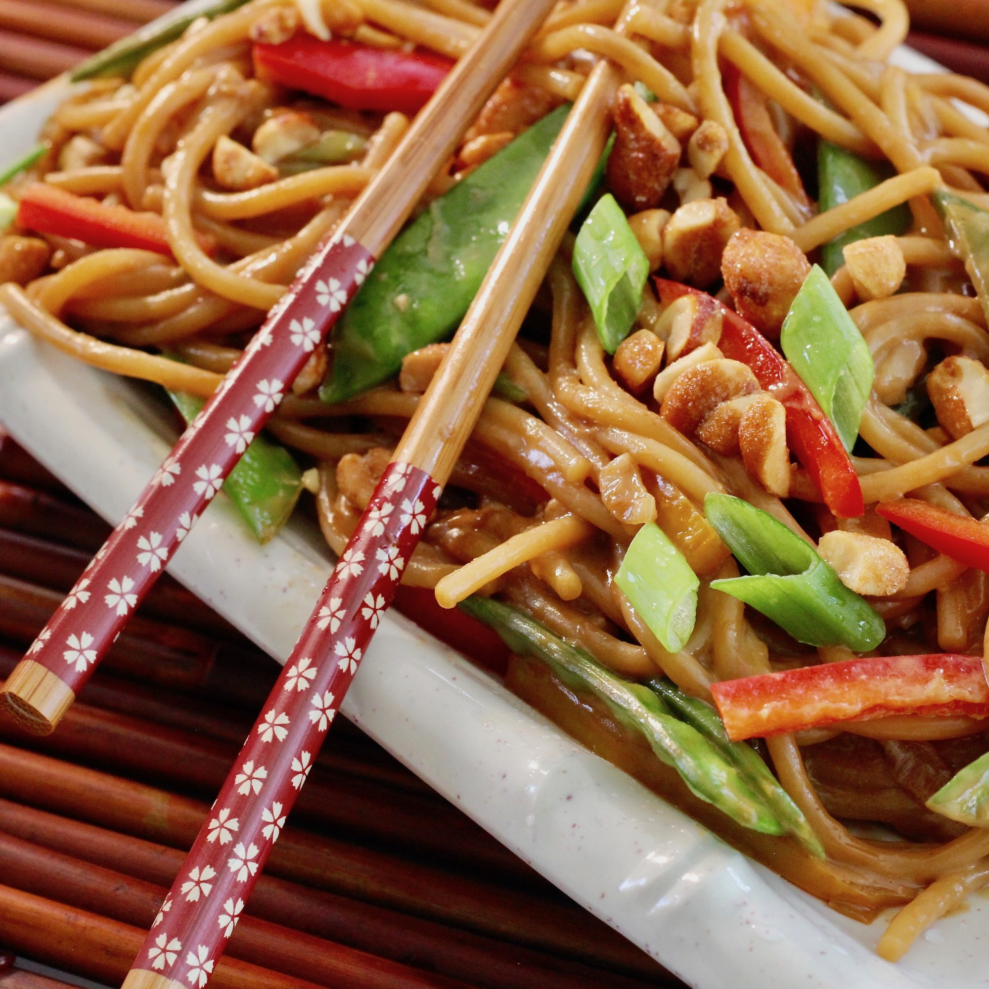 Peanut Noodles with bell peppers on a white plate with chopsticks