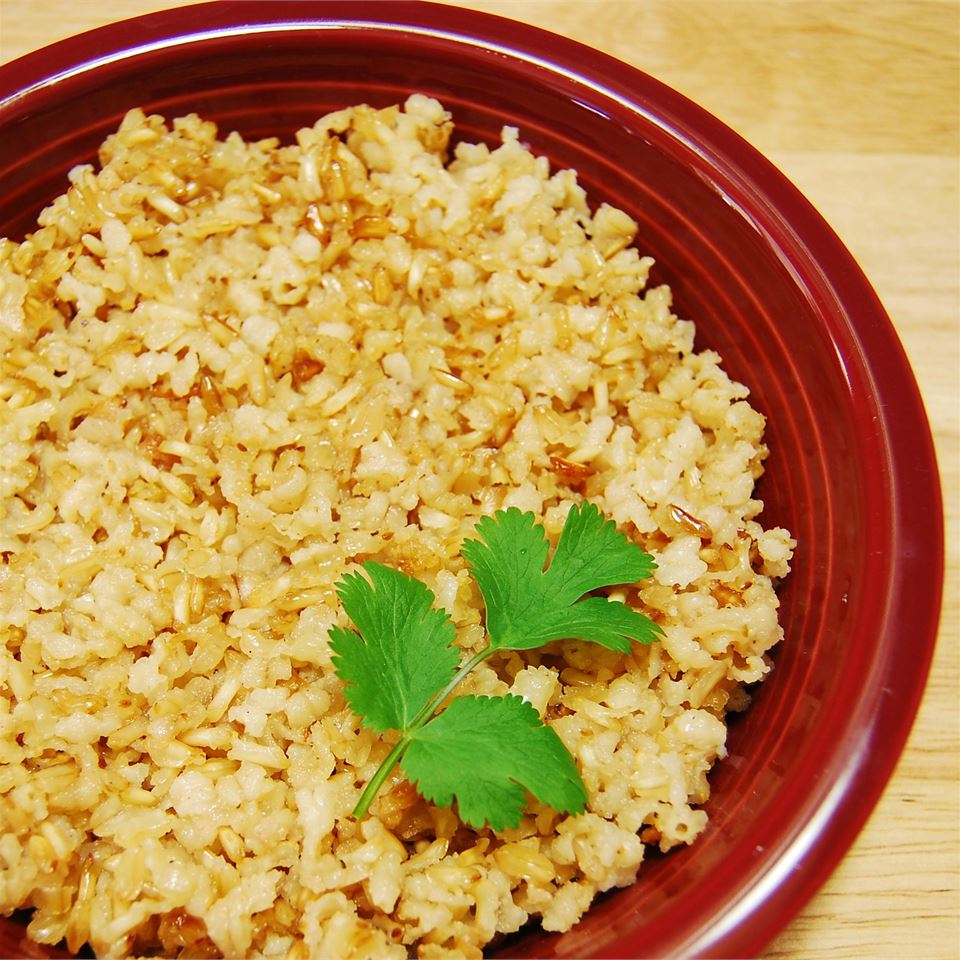a red ceramic bowl of brown rice with a cilantro sprig garnish