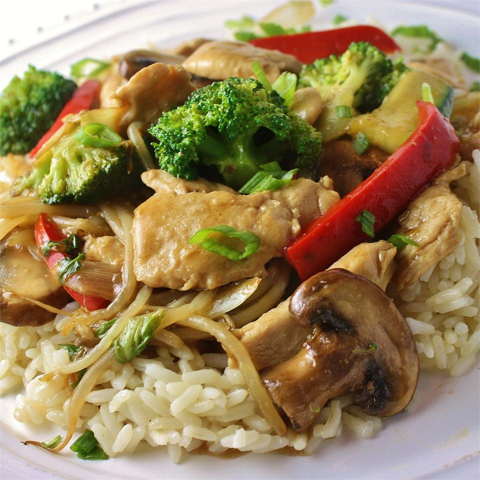 a colorful stir-fry of chicken breast strips, red bell pepper, broccoli florets, and sliced mushrooms on white rice