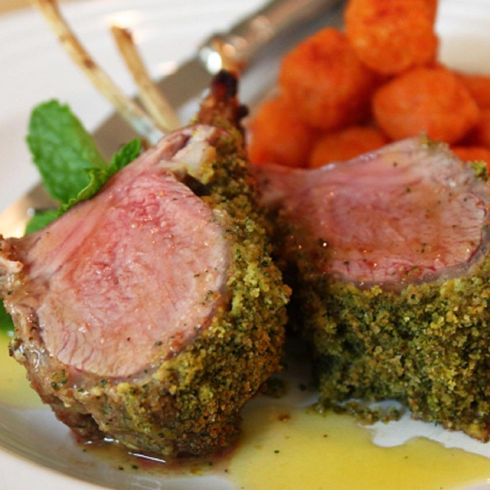 Two lamb chops on a plate with glazed carrots and a mint garnish