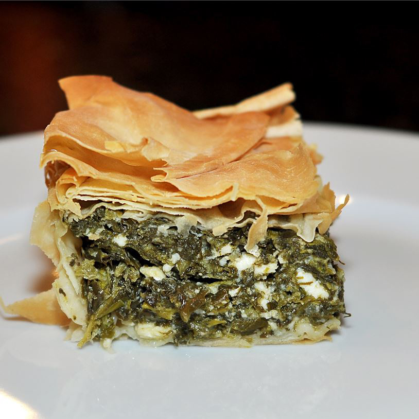 side view of a square of spanakopita on a white plate