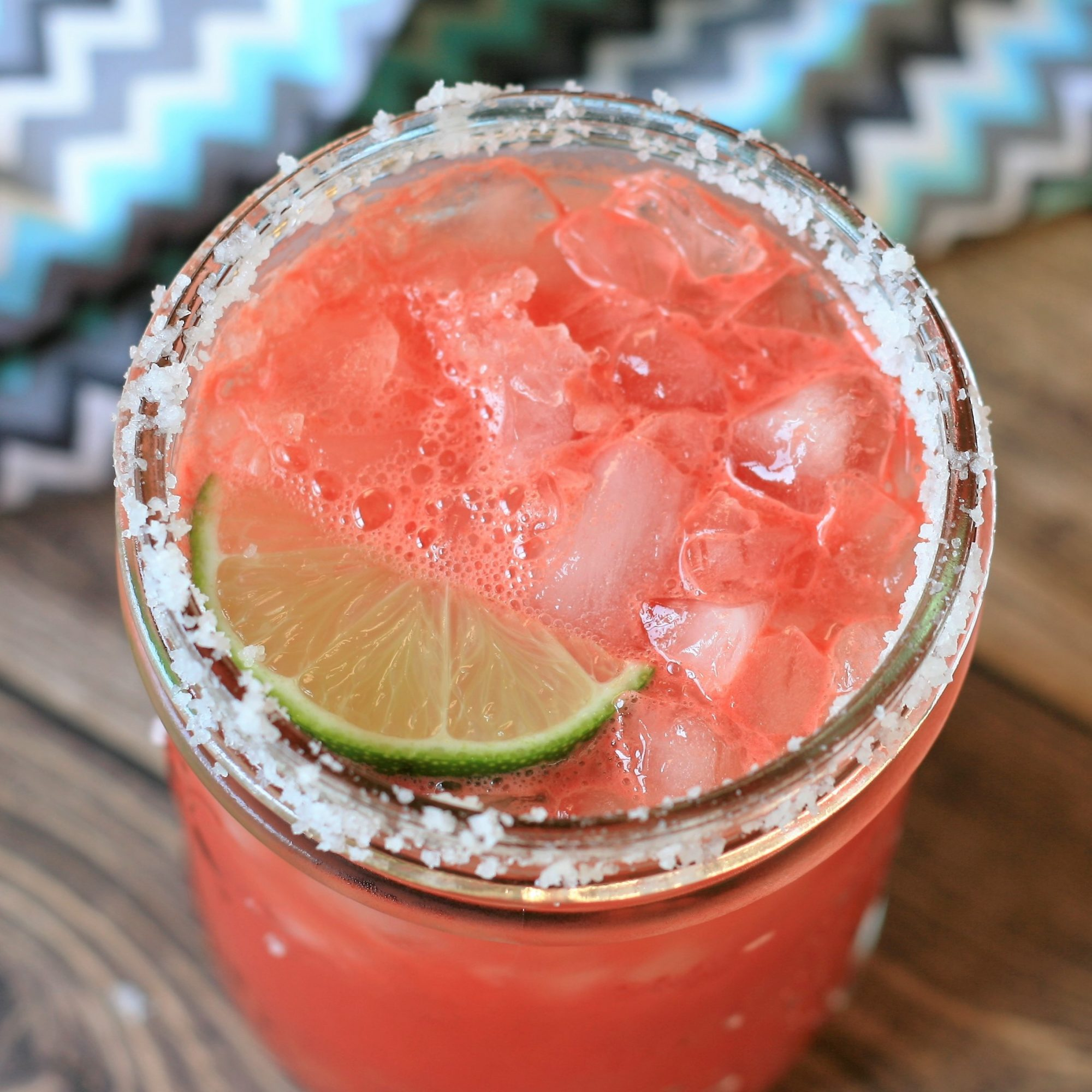 watermelon margarita on the rocks with lime garnish