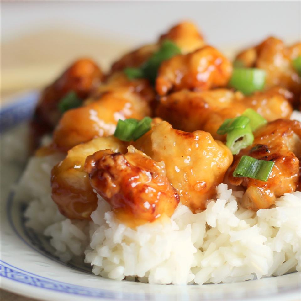 Asian Orange Chicken with rice on a white and blue plate