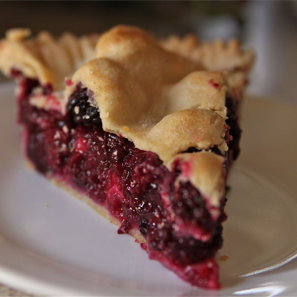 a closeup view of a slice of double-crust blackberry pie on a white plate